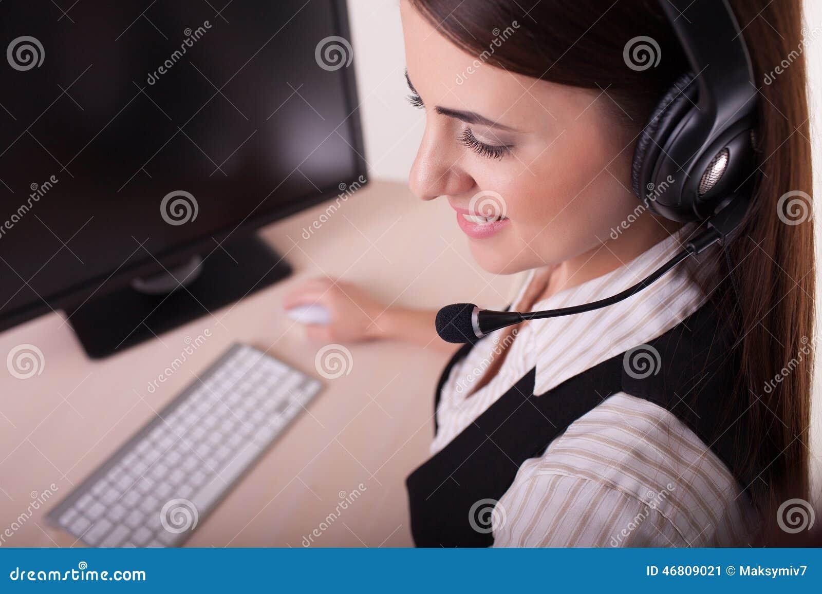Onderneemster met hoofdtelefoon die aan computer werken
