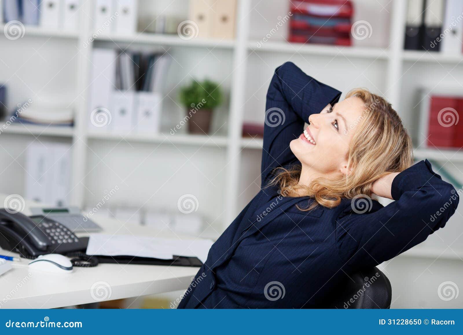 Onderneemster Relaxing With Hands achter Hoofd bij Bureau