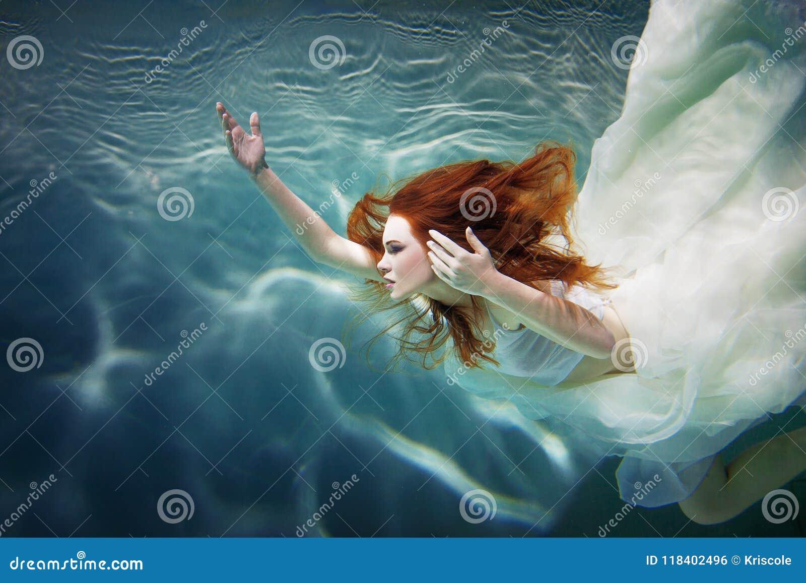 Onderwatermeisje Mooie roodharige vrouw in een witte kleding, die onder water zwemmen