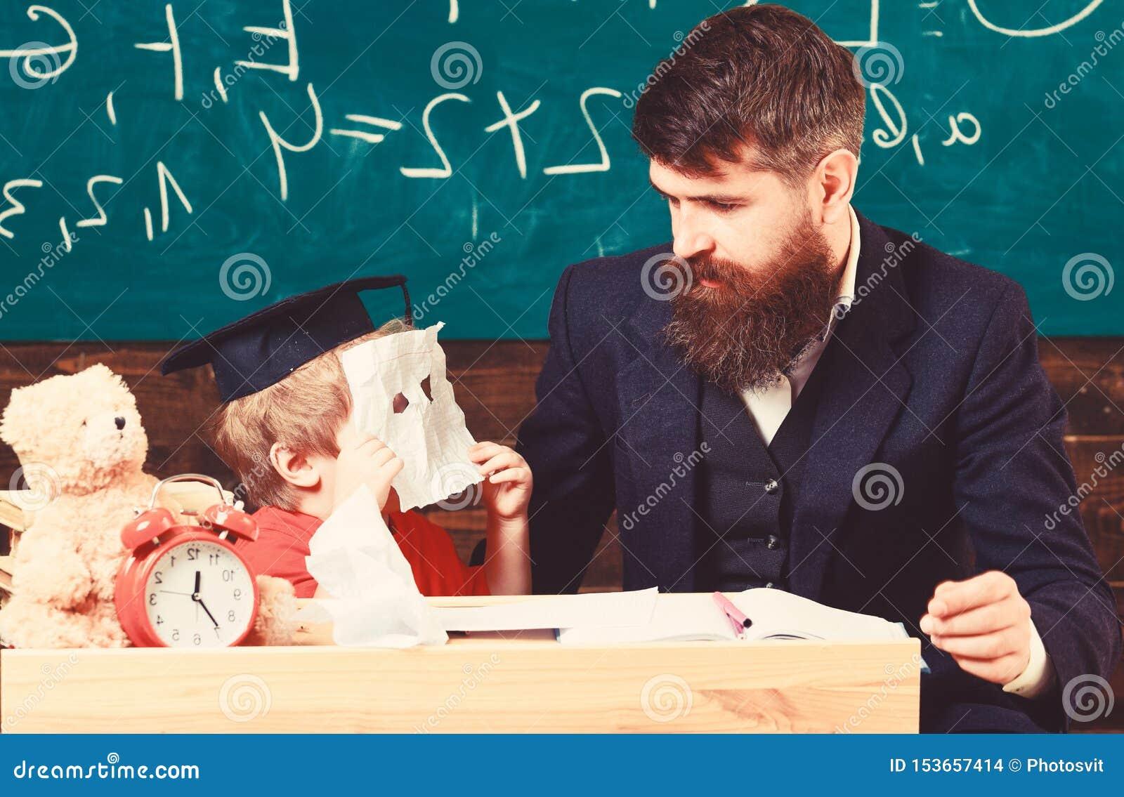 Onderwijs concept Knappe leraar en een kleine jongenszitting voor een groene raad Jong geitje in graduatie GLB het verbergen