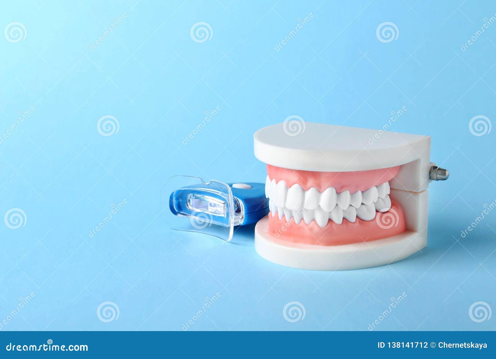 Onderwijsmodel van mondholte met tanden en het witten van apparaat op kleurenachtergrond