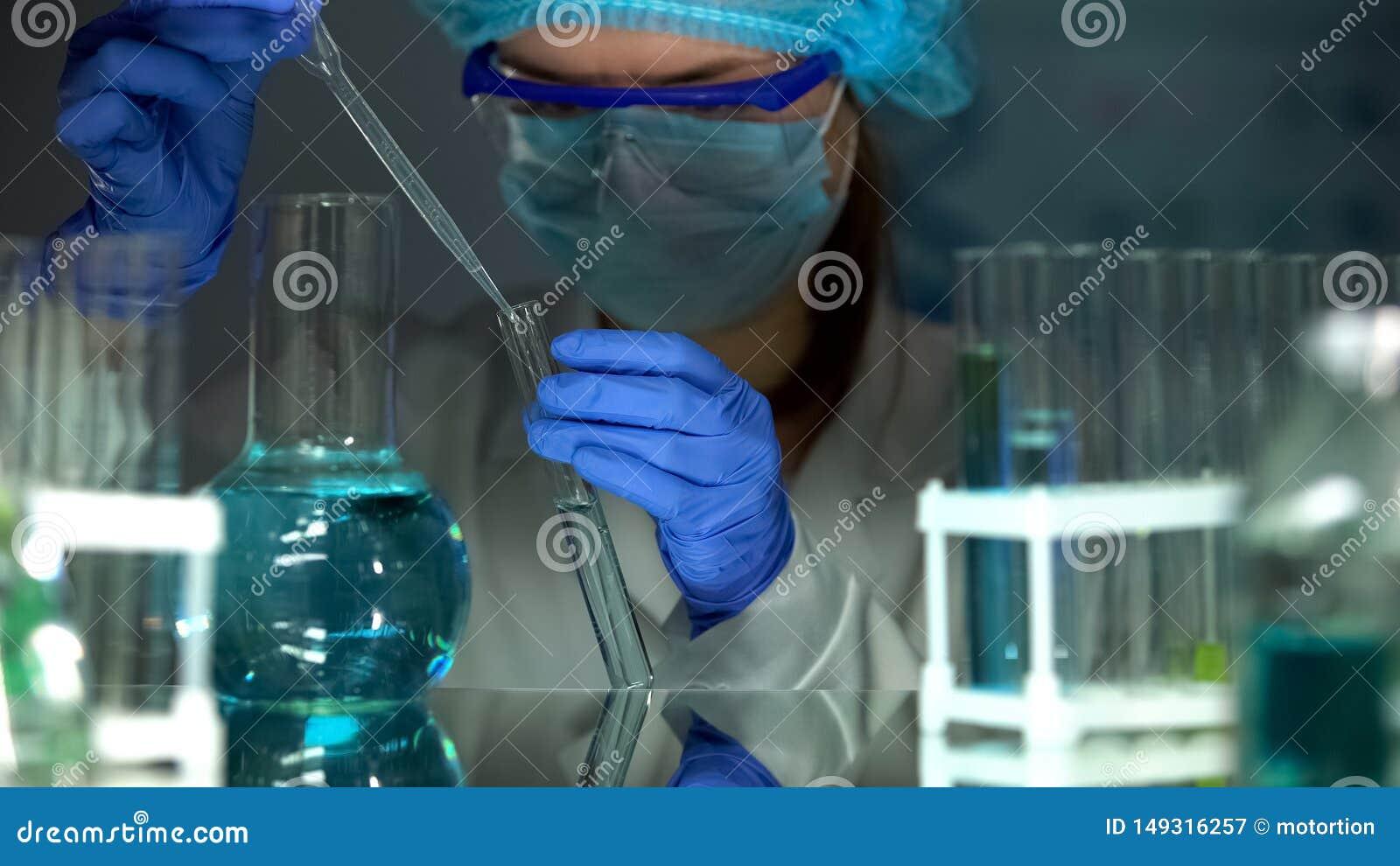 Onderzoekers druipende vloeistof in reageerbuis, met watersteekproef, die PH niveau controleren