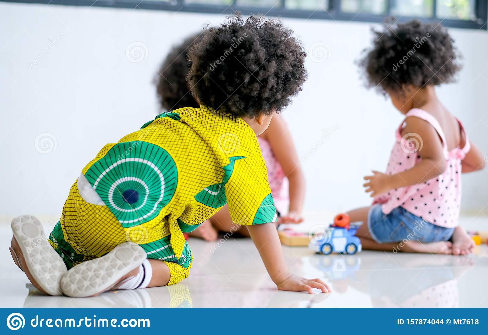 One African Boy Look At Two Girls Play Toys Together And Look Like