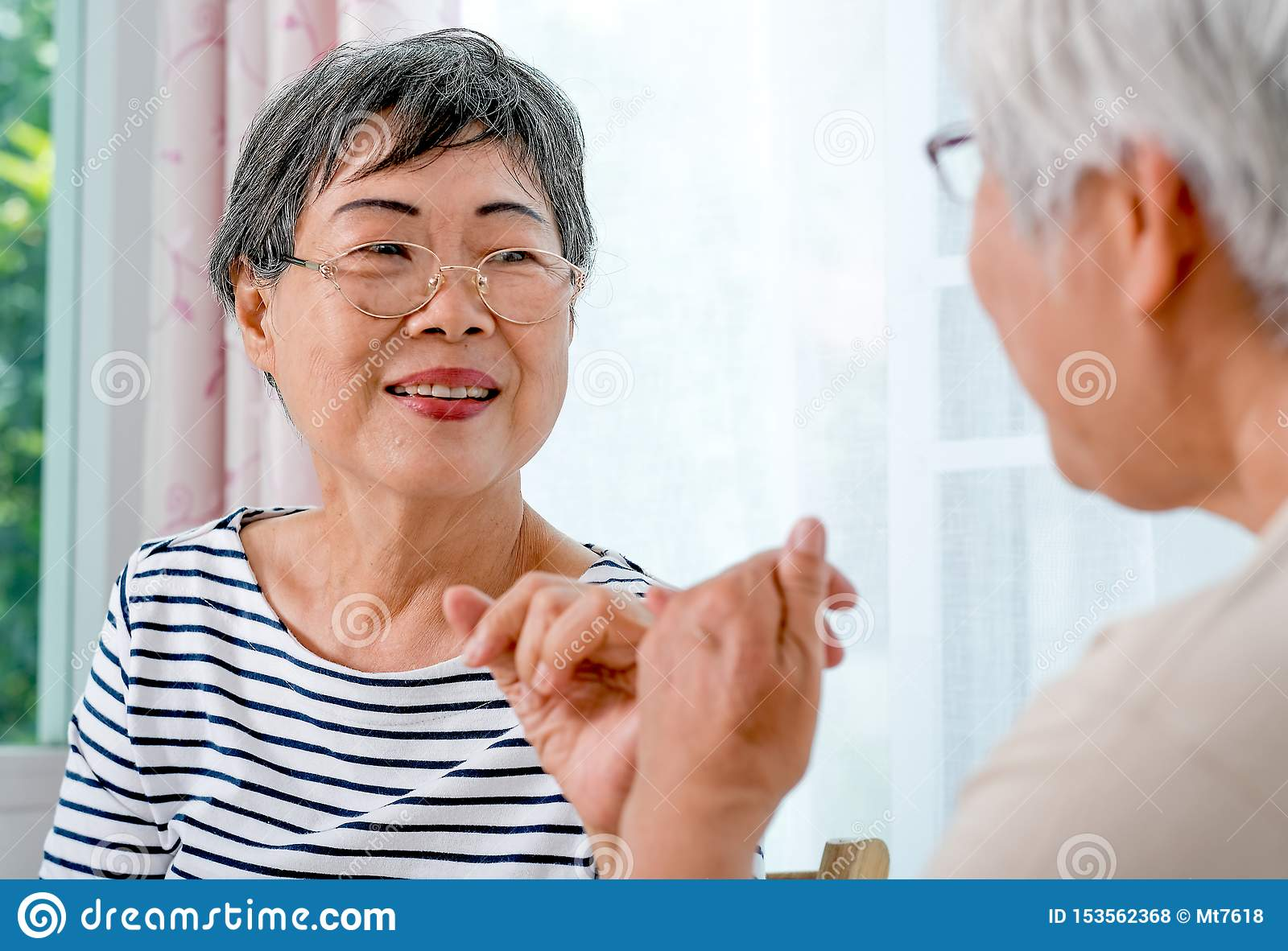 One Asian elderly woman hook each others little finger to the other with smiling in front of balcony in the house