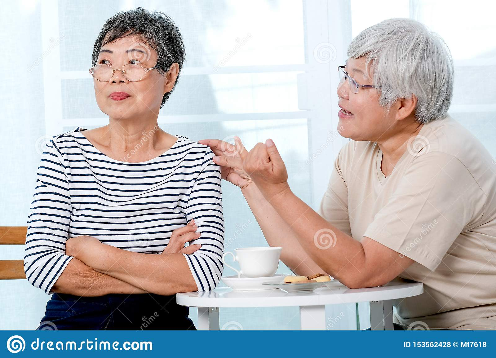 One Asian elderly woman try to reconcile to the other one during the tea time near balcony in the house