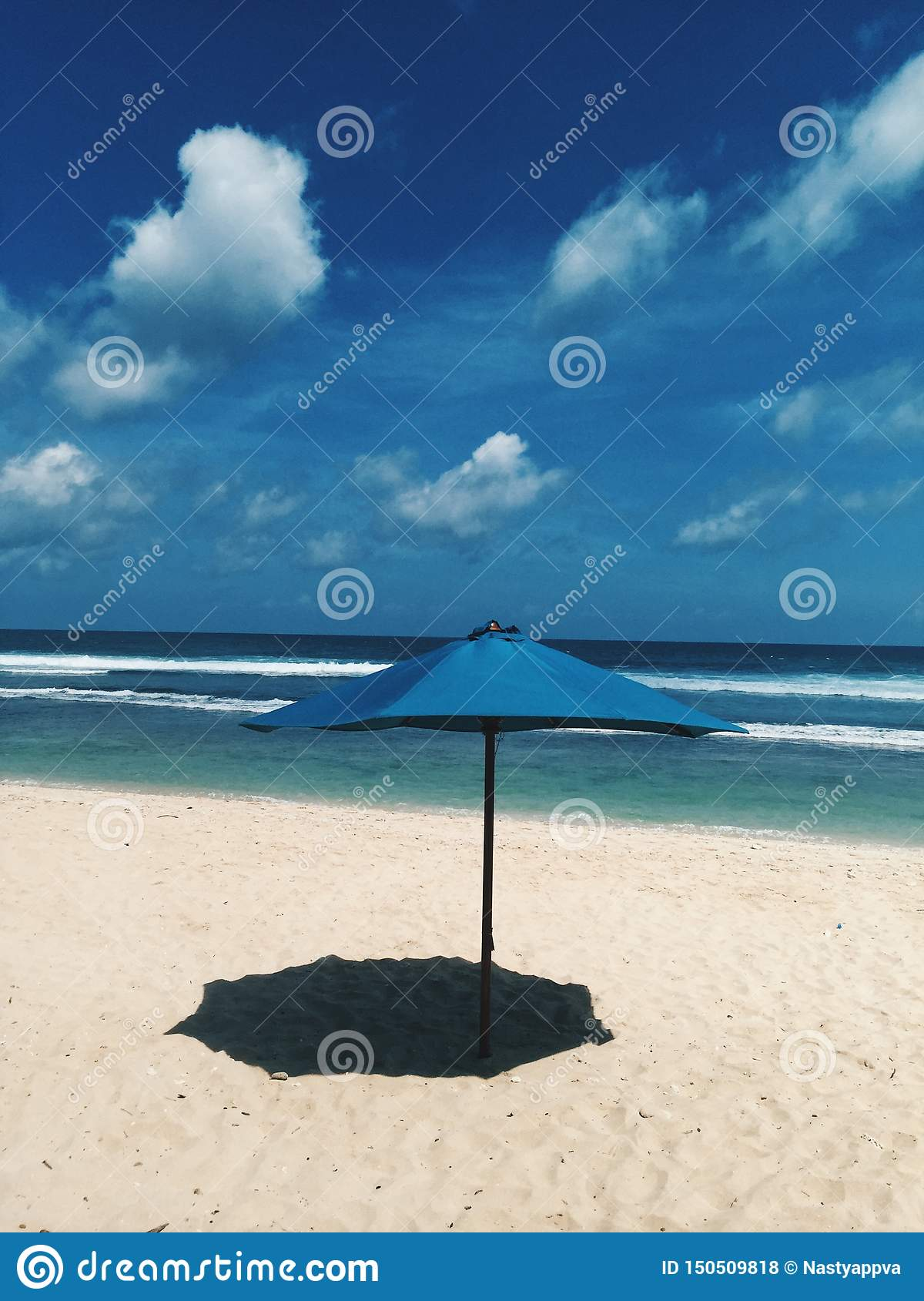 One blue beach sun umbrella make shade on the sand