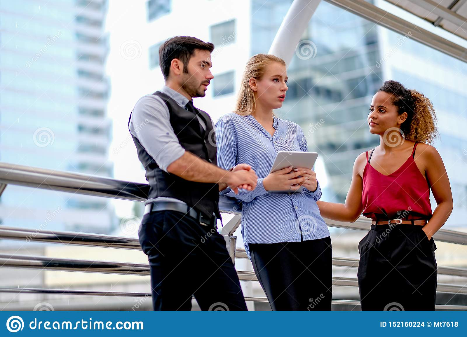 One business man discuss about work with his team, two women with one mixed race tan skin and white Caucasian woman who holds