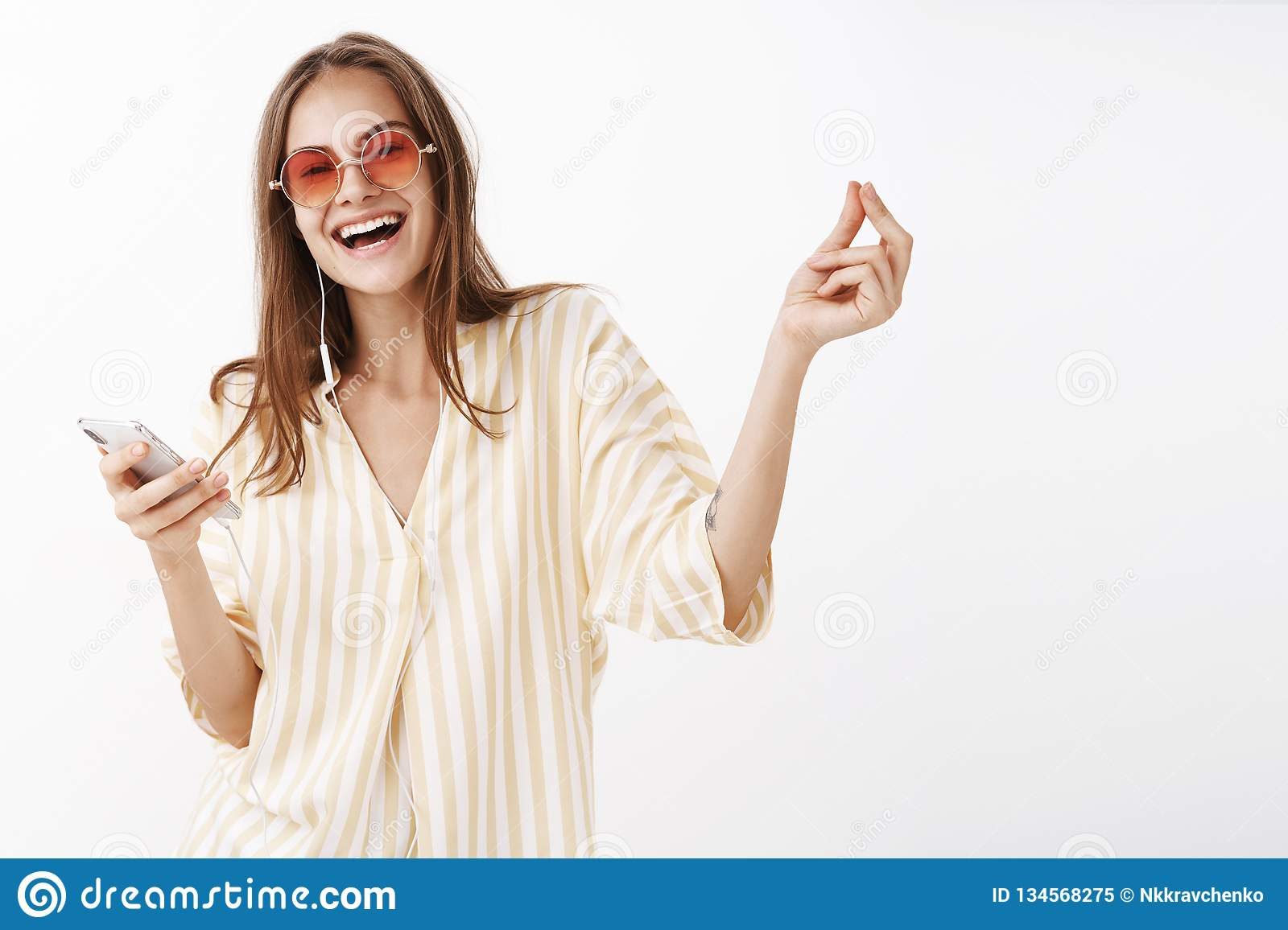 One click and go. Portrait of joyful delighted happy woman in trendy sunglasses and blouse holding smartphone smiling