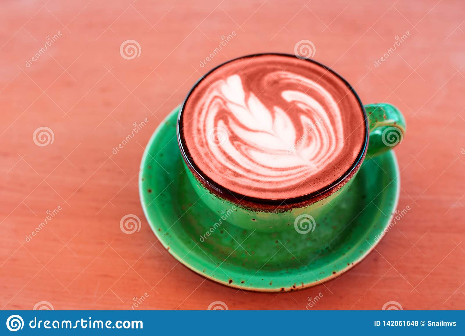 One cup of cappuccino with latte art of Living Coral color on wooden background, greenery ceramic cup, place for text.