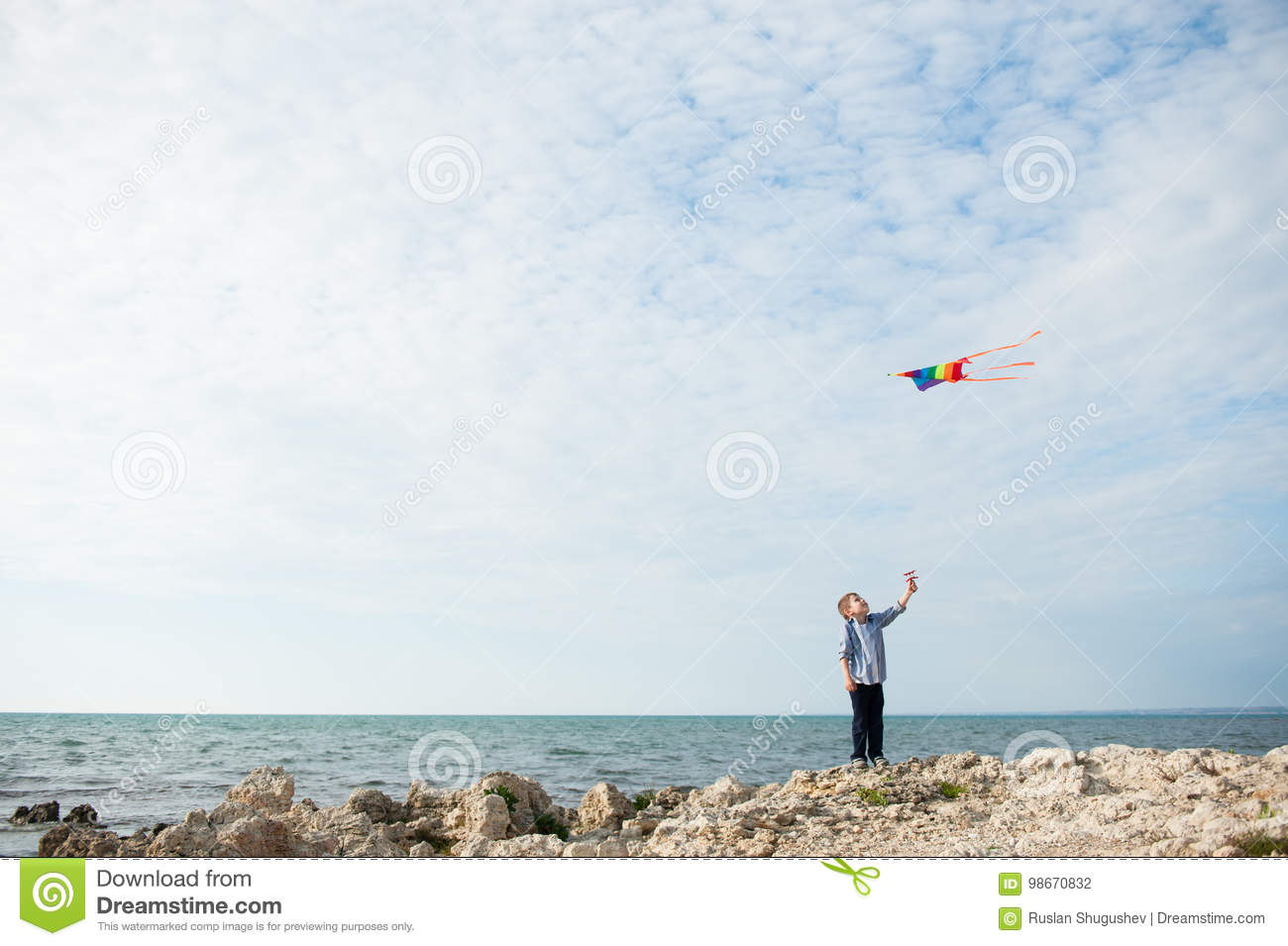 One Cute Small Boy Holding A Kite Flying In The Sky On The