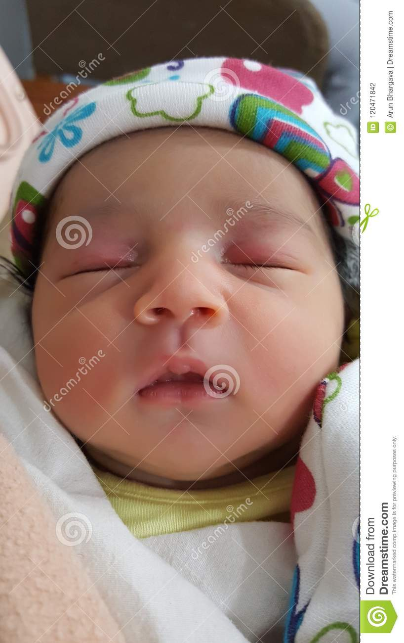 A new born baby with pink cheeks and eye lids sleeps in soft white cloth cover and her delicate hand is out in front