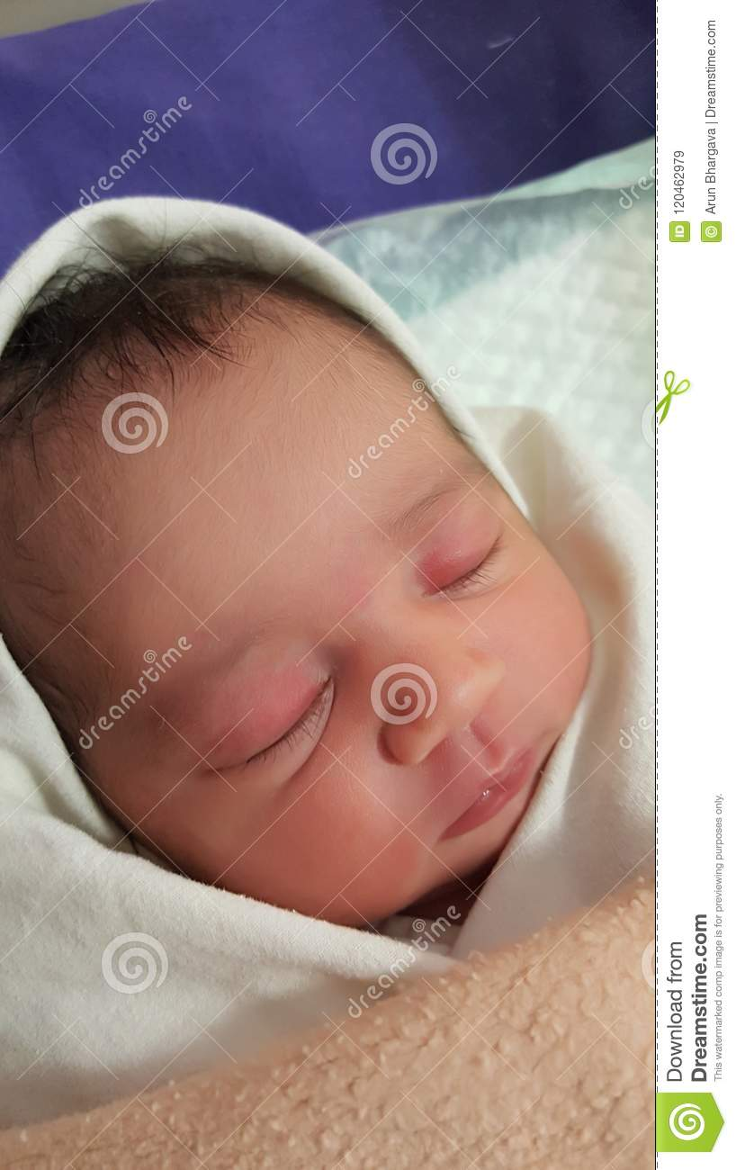 Beautiful indian asian new born baby girl wrapped in soft warm cloth for comfort and safety