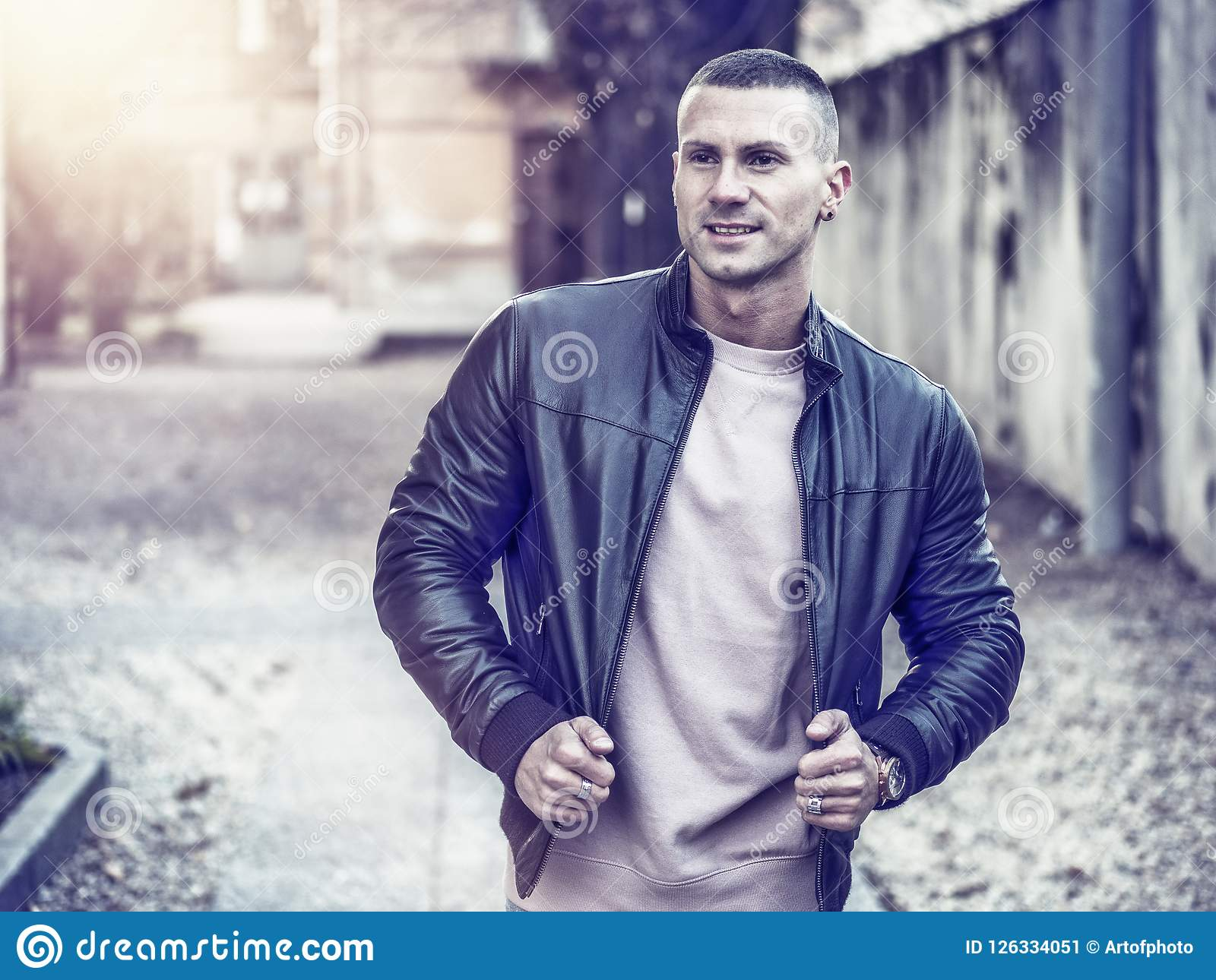 c59e442b One handsome young man in urban setting in European city, standing, wearing  black leather jacket and jeans. More similar stock images
