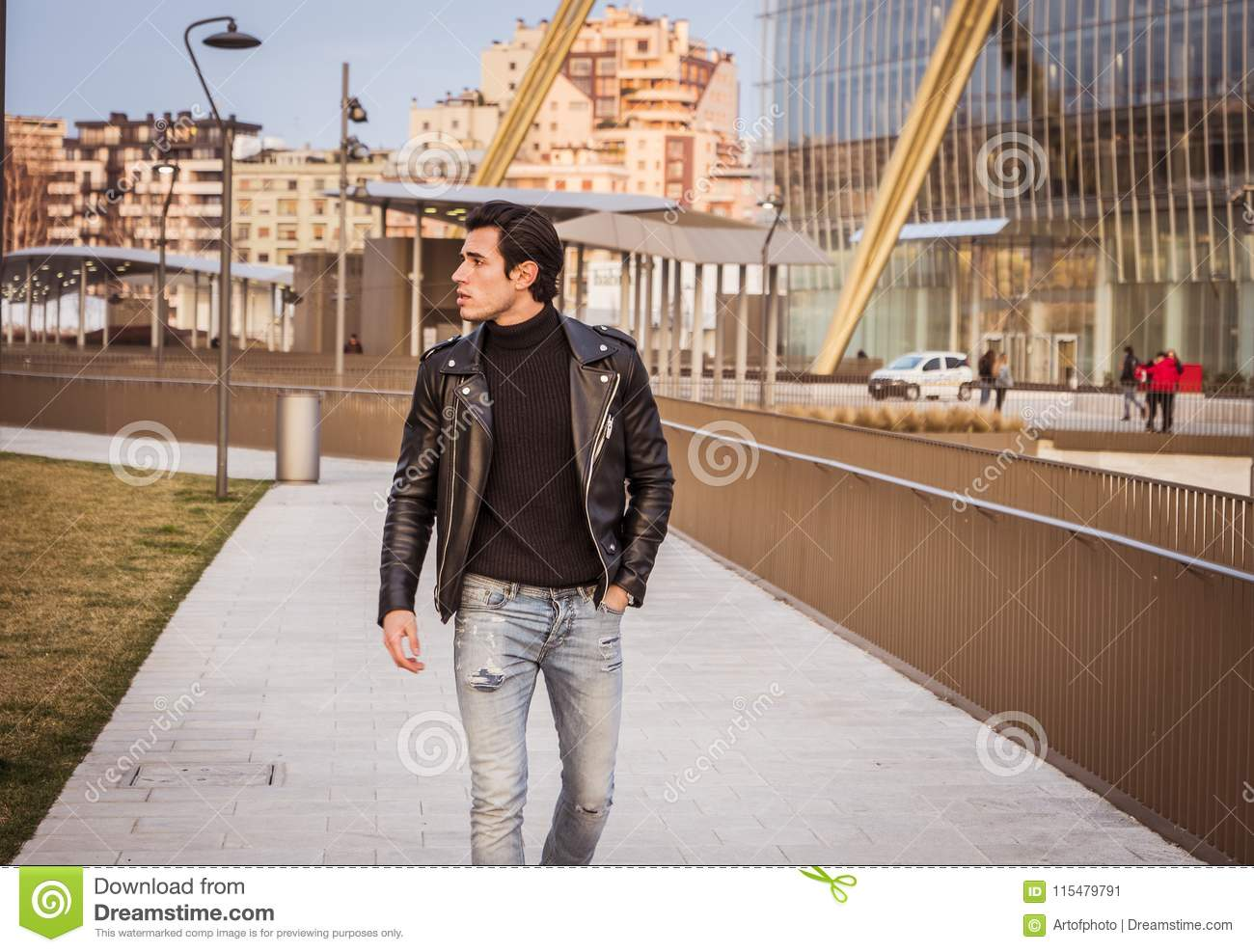 7ea6a8e1 One handsome young man in urban setting in modern city, standing, wearing  black leather jacket and jeans. More similar stock images
