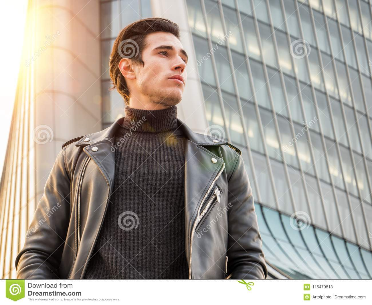 9add8409 One handsome young man in urban setting in modern city, standing, wearing  black leather jacket and jeans
