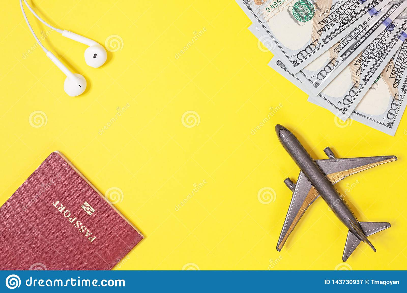 One hundred dollar bills, airplane, headphones, foreign passport on bright yellow paper background. Copy space.