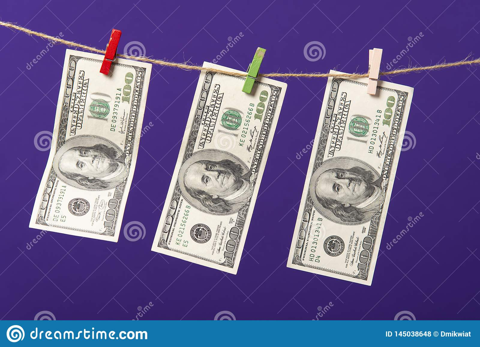 One hundred dollars hanging on clothesline with wooden clips on blue background