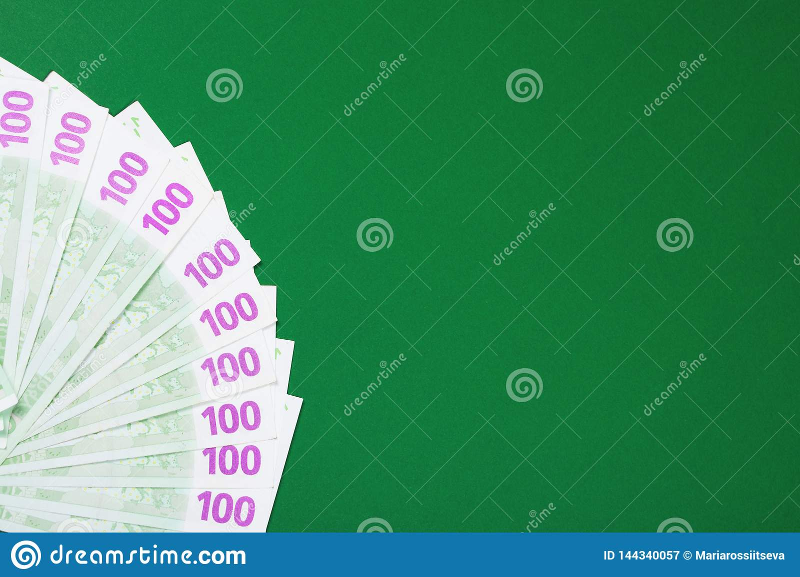 One hundred euro notes on green background