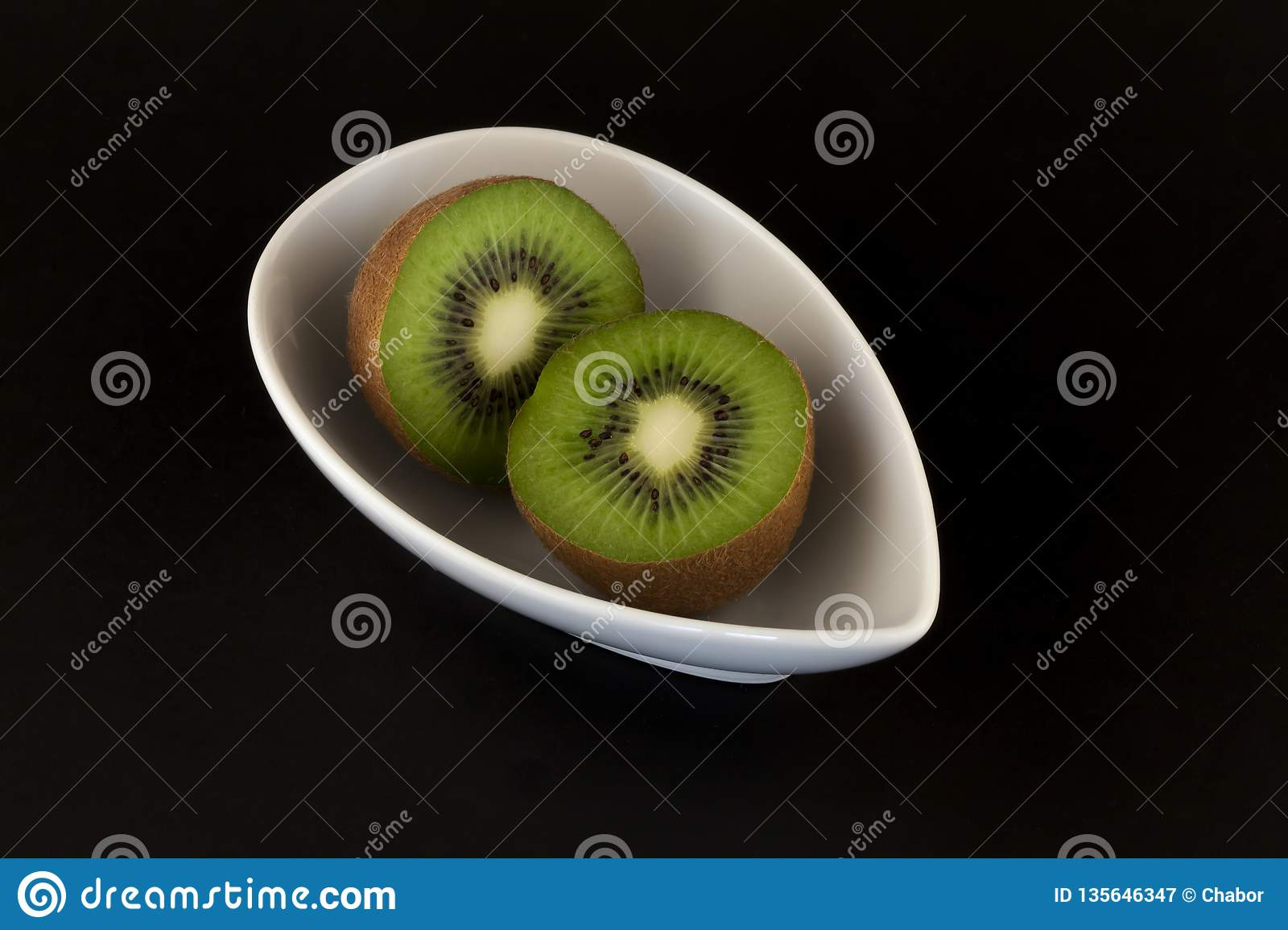 Kiwis in white bowl on black background