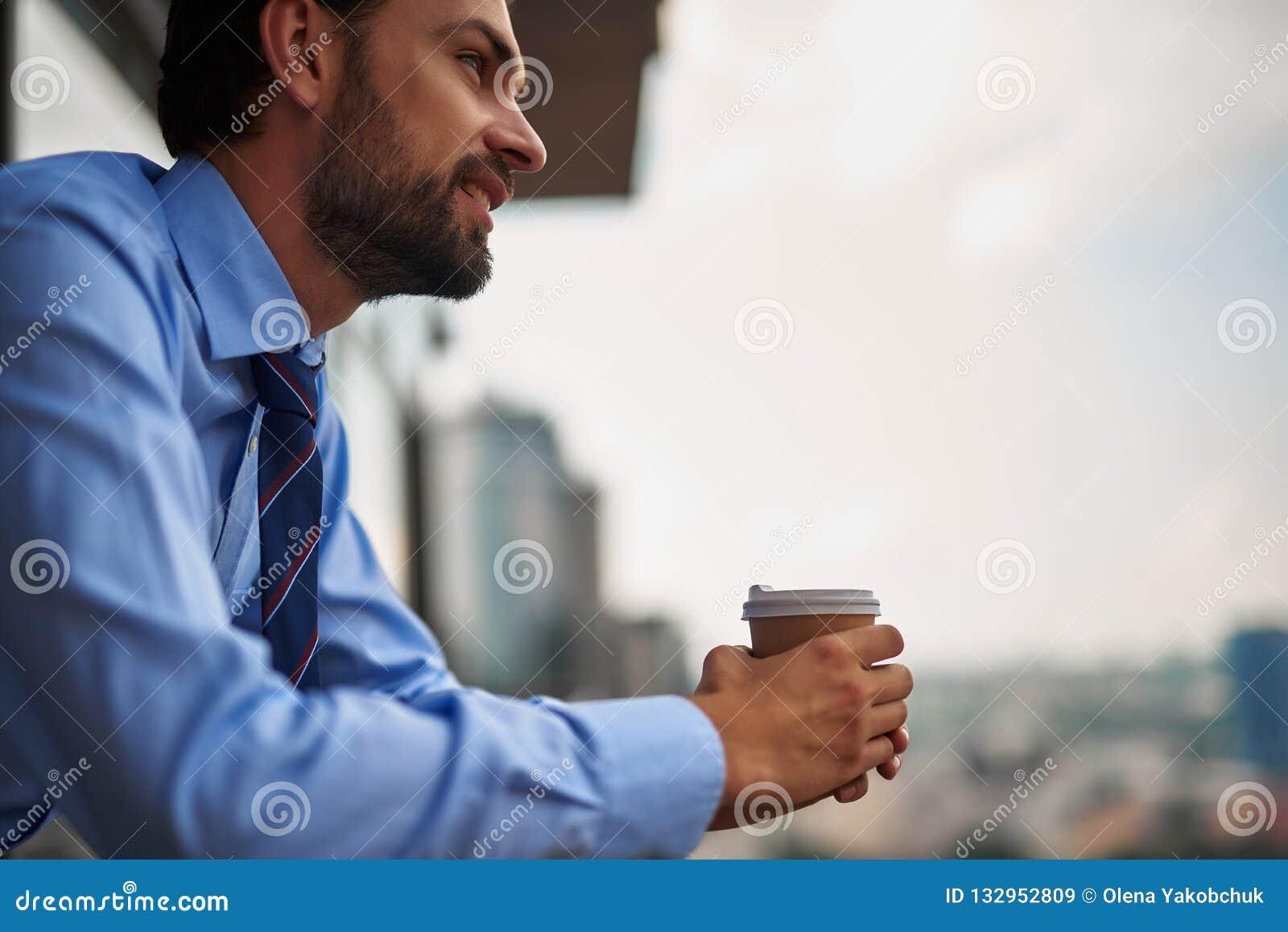 One male worker drinking coffee on office balcony