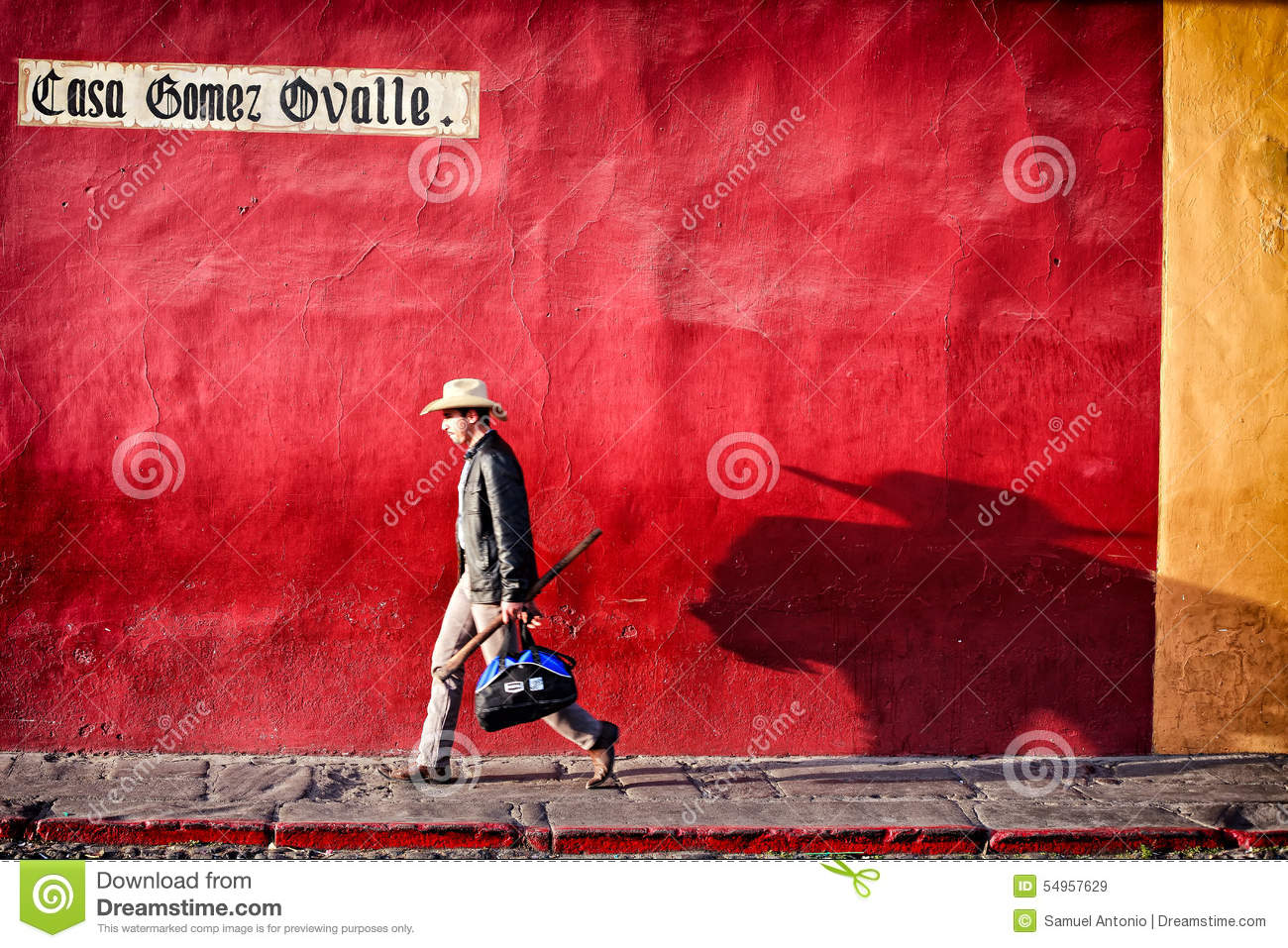One Man Walking Along Colorful Wall With His Shadow