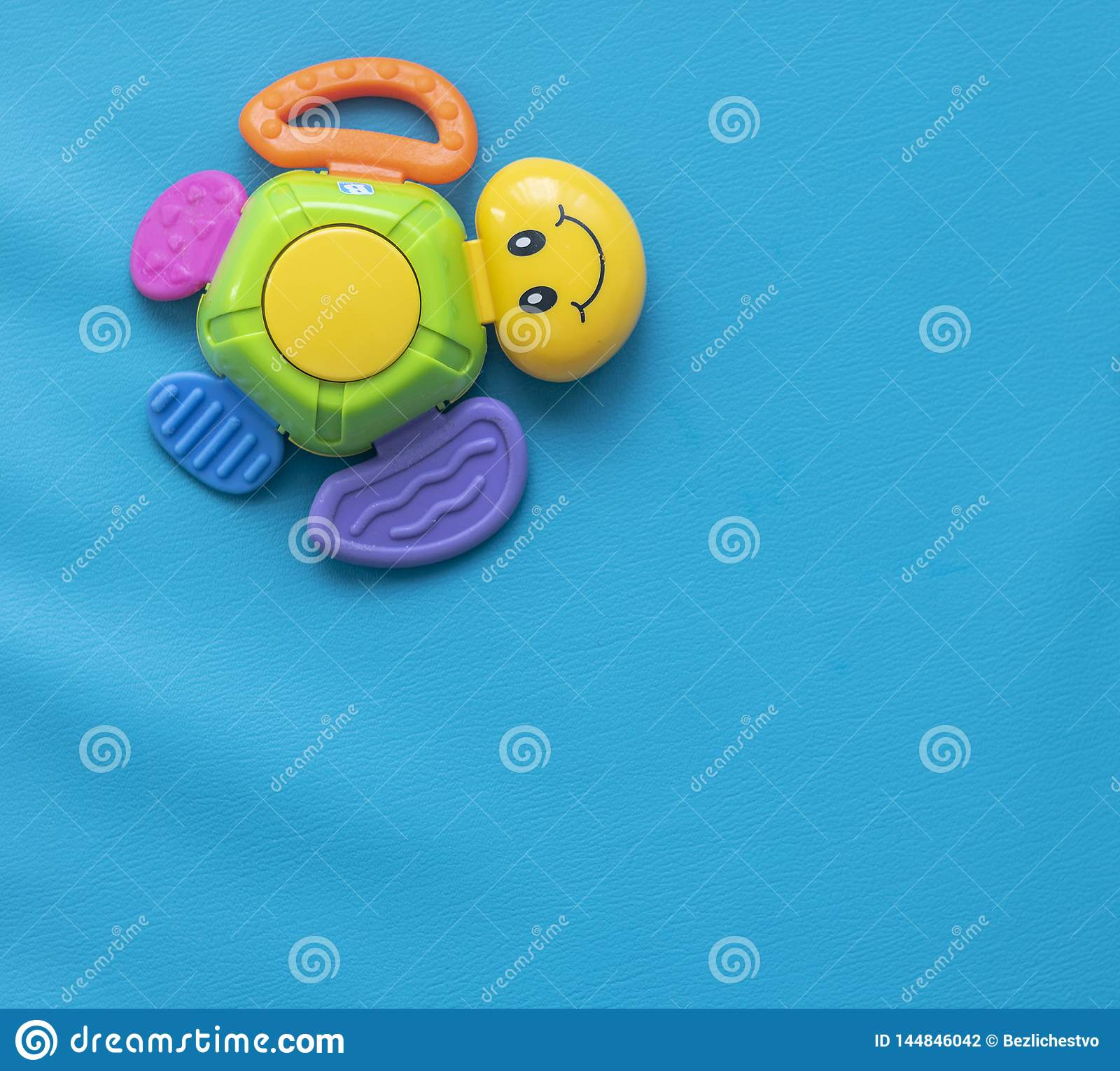 One multi-colored toy turtle with a smile on a blue background to the left