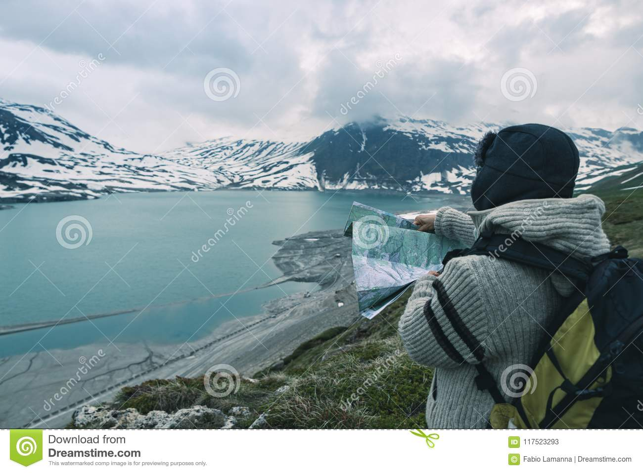 One person looking at trekking map, dramatic sky at dusk, lake and snowy mountains, nordic cold feeling