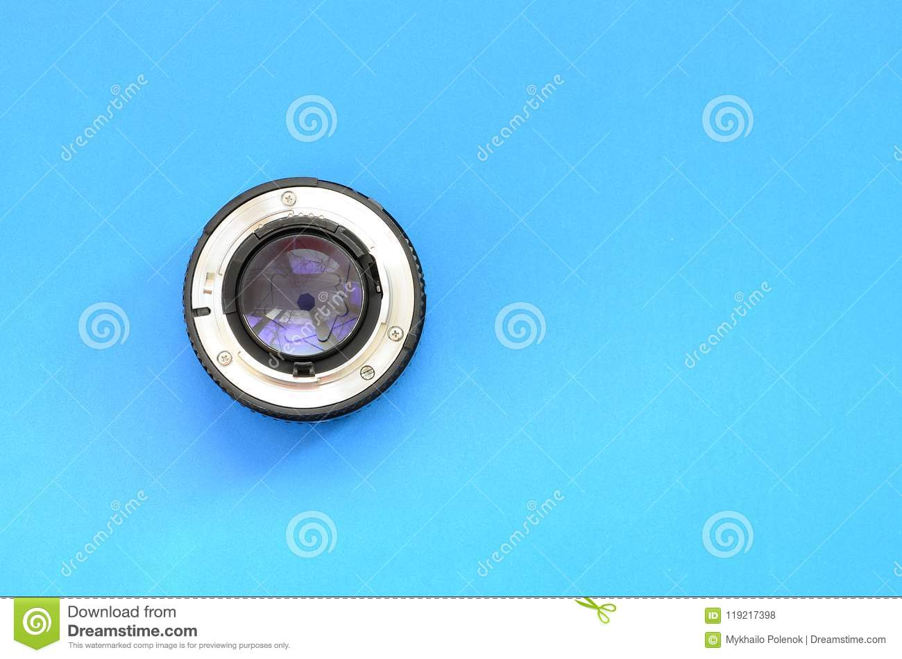 One photographic lense lie on a bright blue background. Space fo