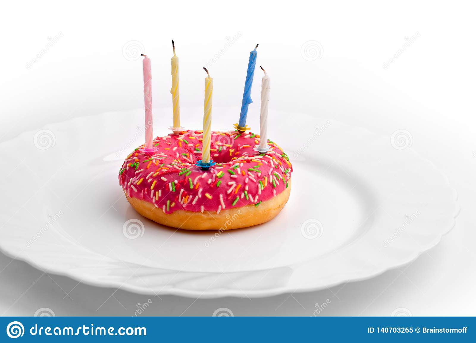 Pink donut on white plate like birthday cake with candles on white background
