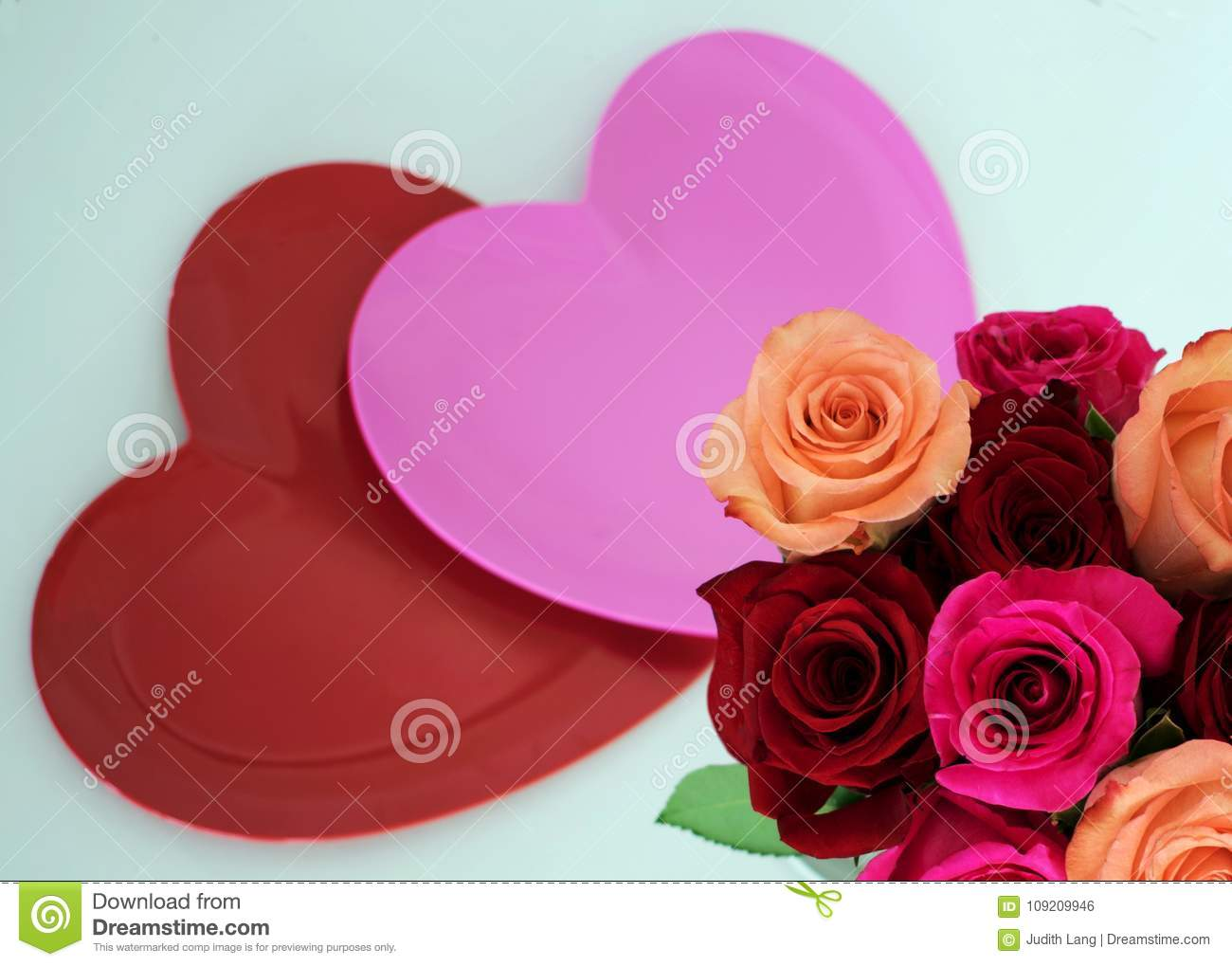 One pink and one red heart with roses in lower right