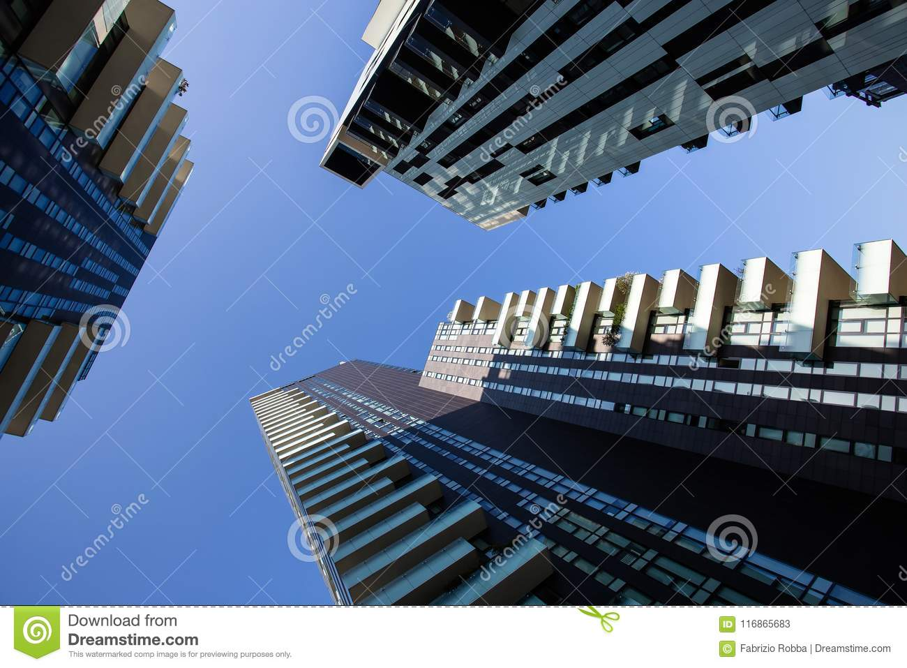 One point perspective looking straight up towards clear blue sky from ground level of tall skyscraper buildings in Milan, Italy