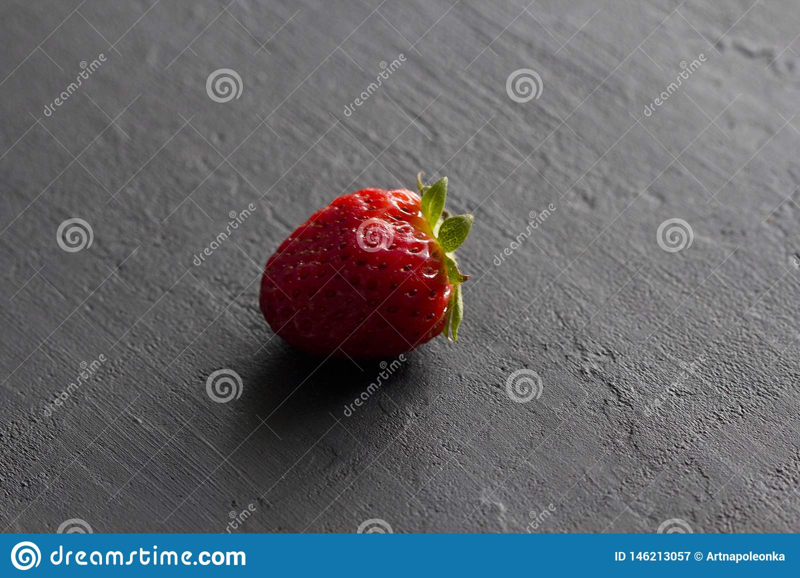 One red beautiful strawberry close-up, on a black dark concrete background. Minimalism. Side view, Copy Space For Your Text. Macro