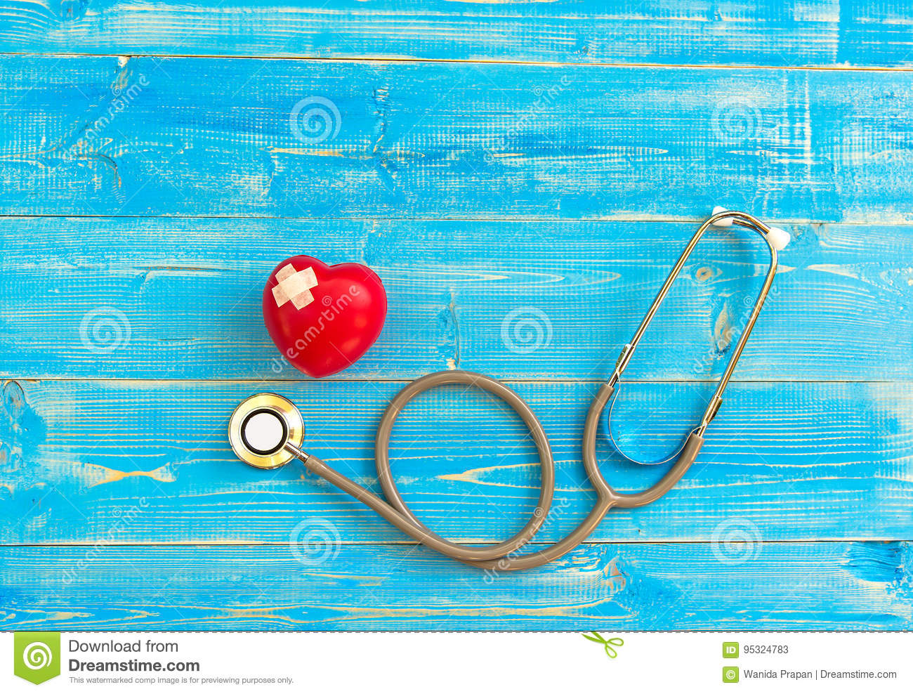 One single alone red heart love shape hand exercise ball with bandage MD medical doctor physician`s stethoscope blue wood backgro