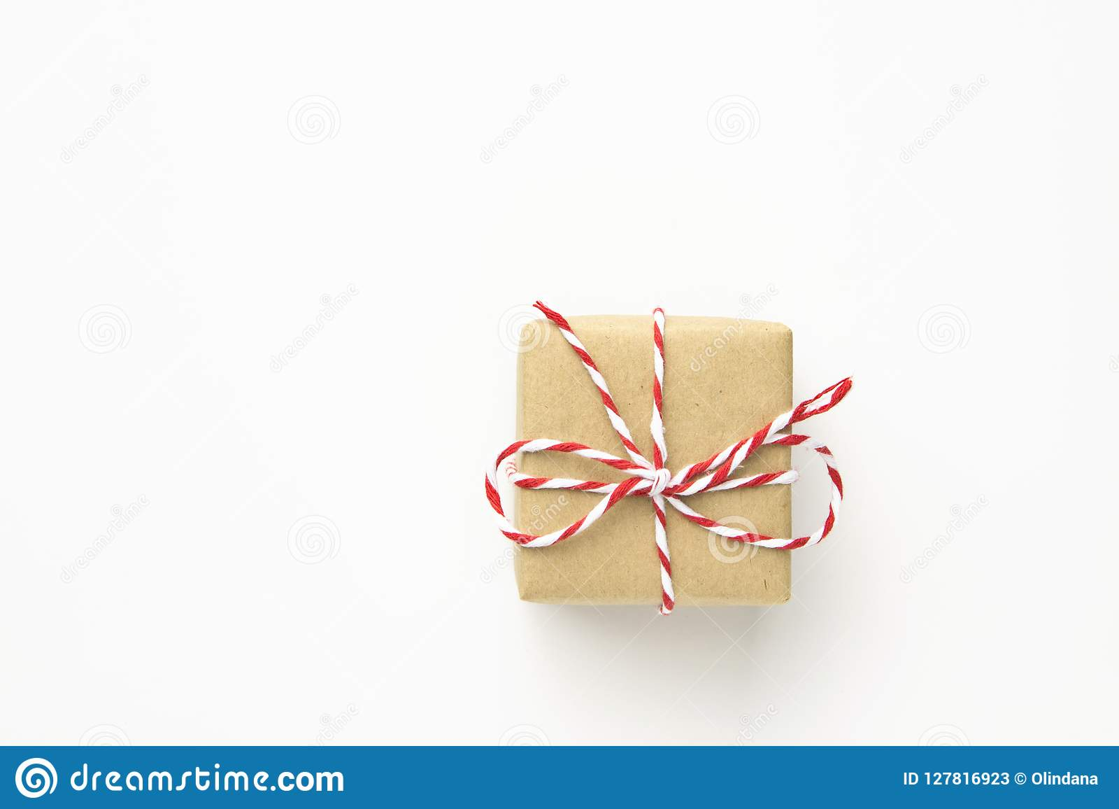 One Small Gift Box Wrapped In Brown Craft Paper Tied With Striped