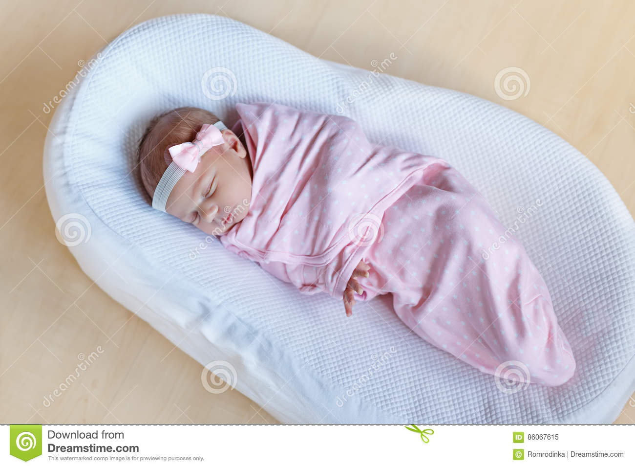 one week old newborn baby girl sleeping wrapped in blanket