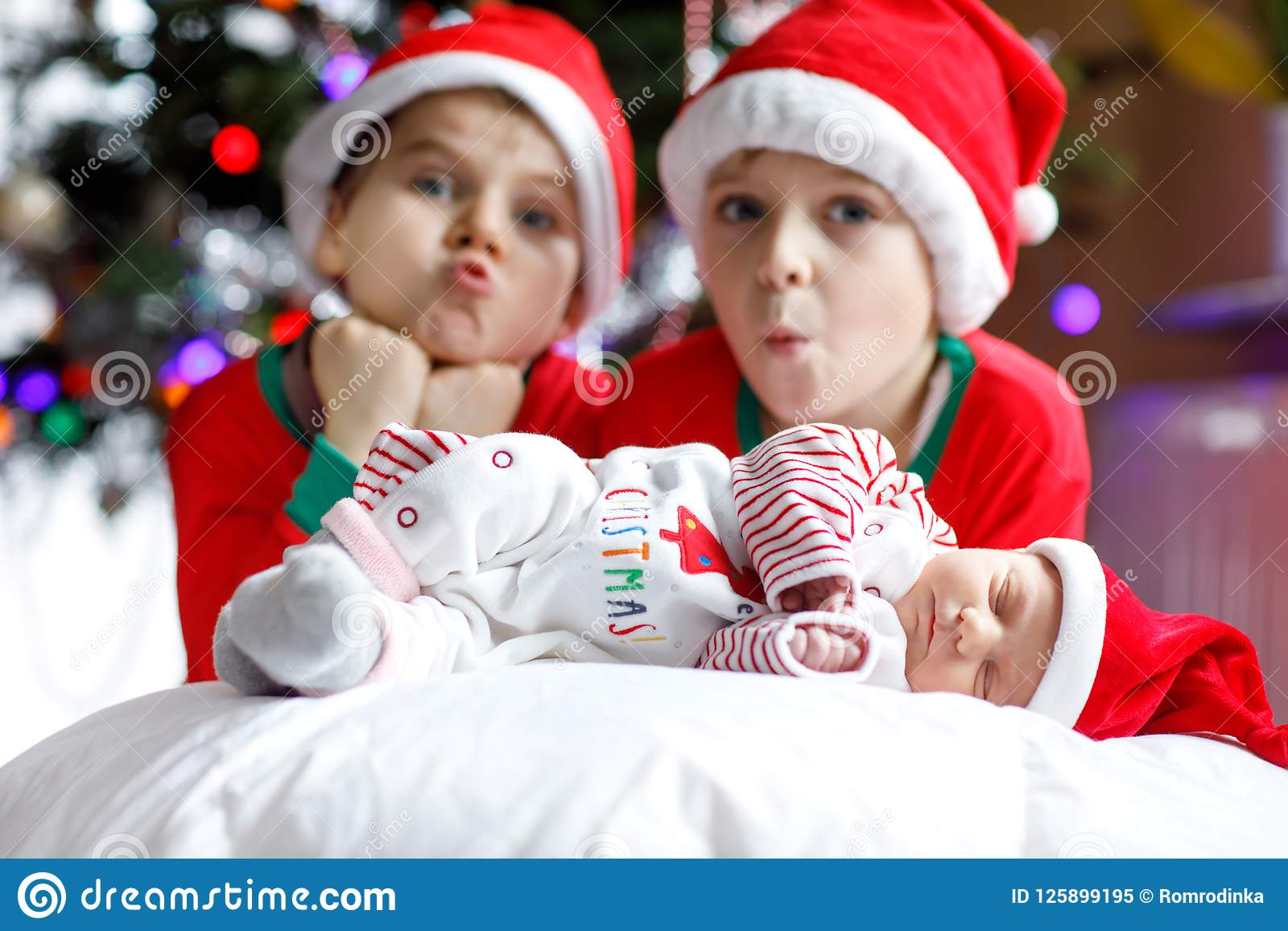bb76756dc3d One week old newborn baby girl and two siblings kid boys in Santa Claus hats  near Christmas tree with colorful garland lights on background.