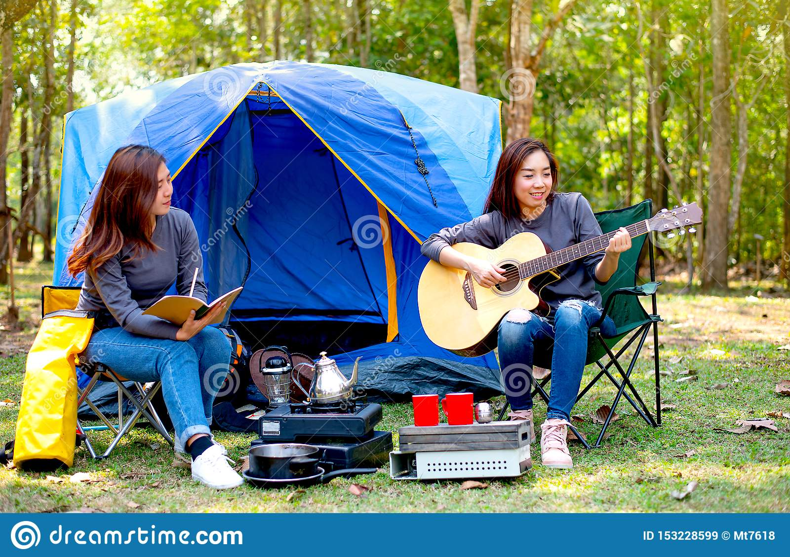 One woman play the guitar while the other one records something during the camping in forest and look like they feel fun and happy