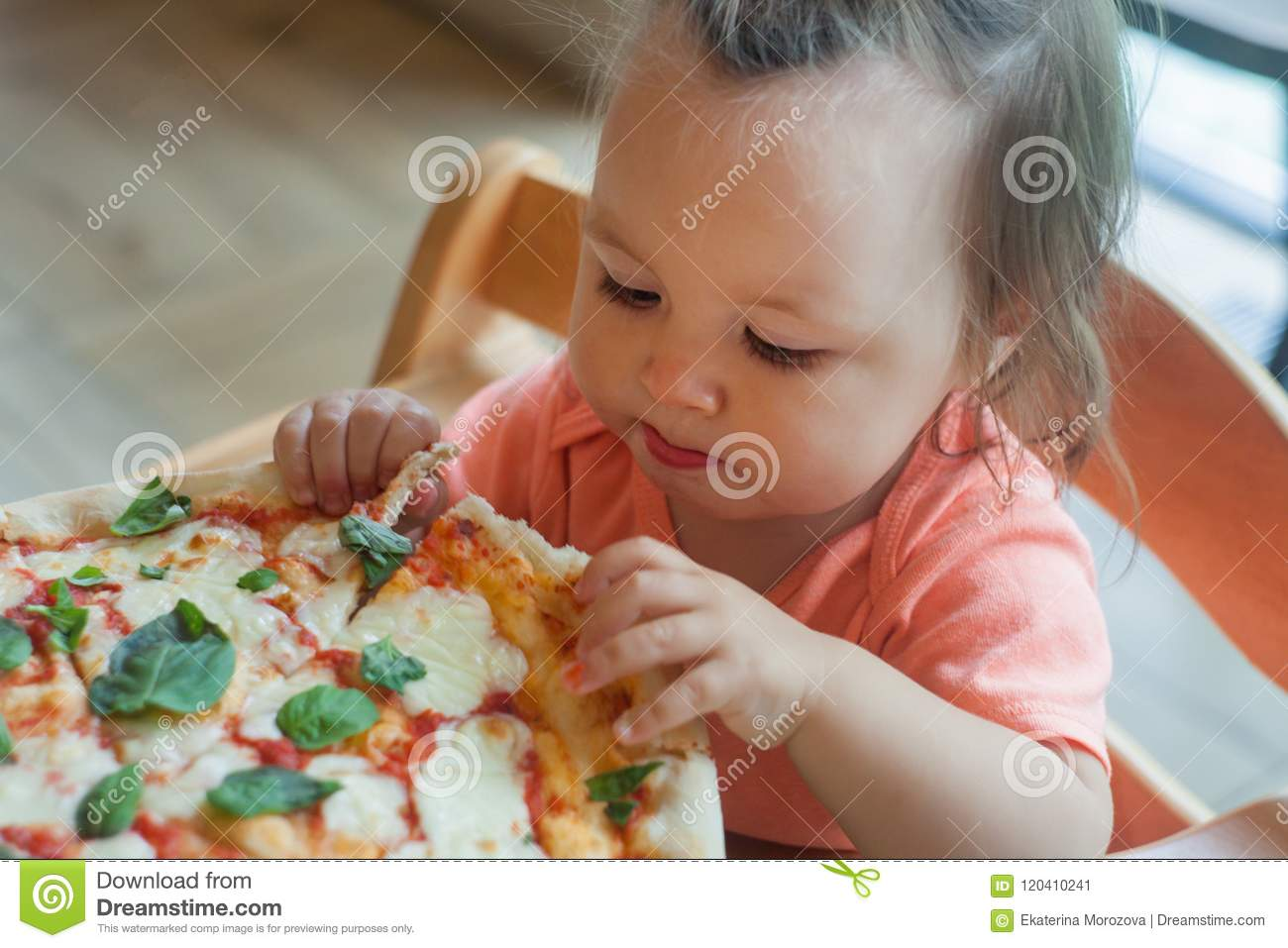 One Year boy sits in director chair in a public cafe indoor and eating italian pizza, children`s fast food.