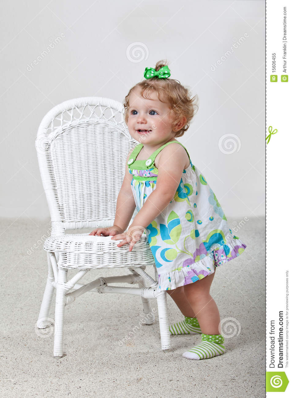 Old baby wearing pink and green standing next to a white wicker chair