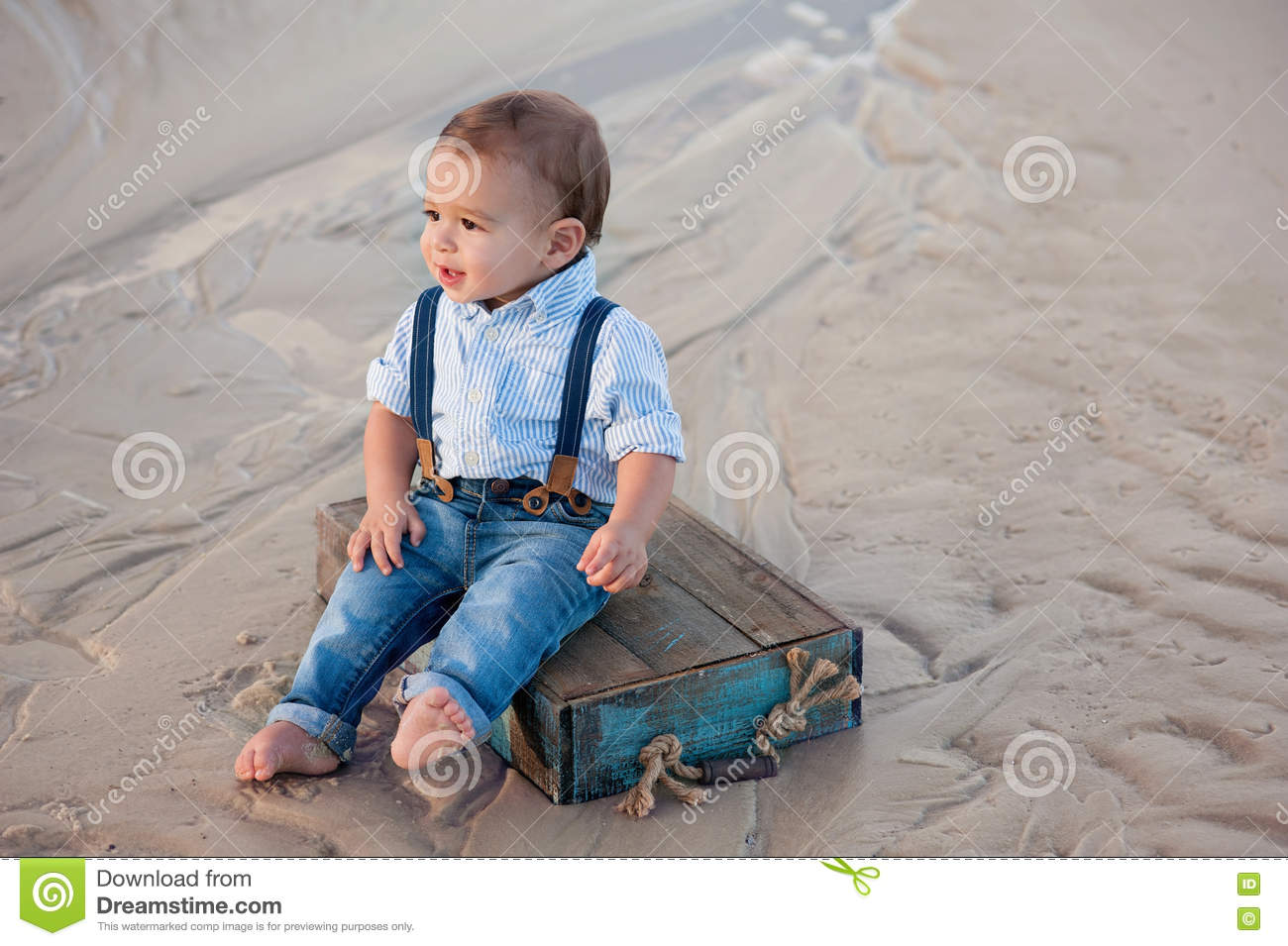 A One Year Old Baby Boy Sitting On Blue Wooden Crate Shot Outdoors Sandy Beach