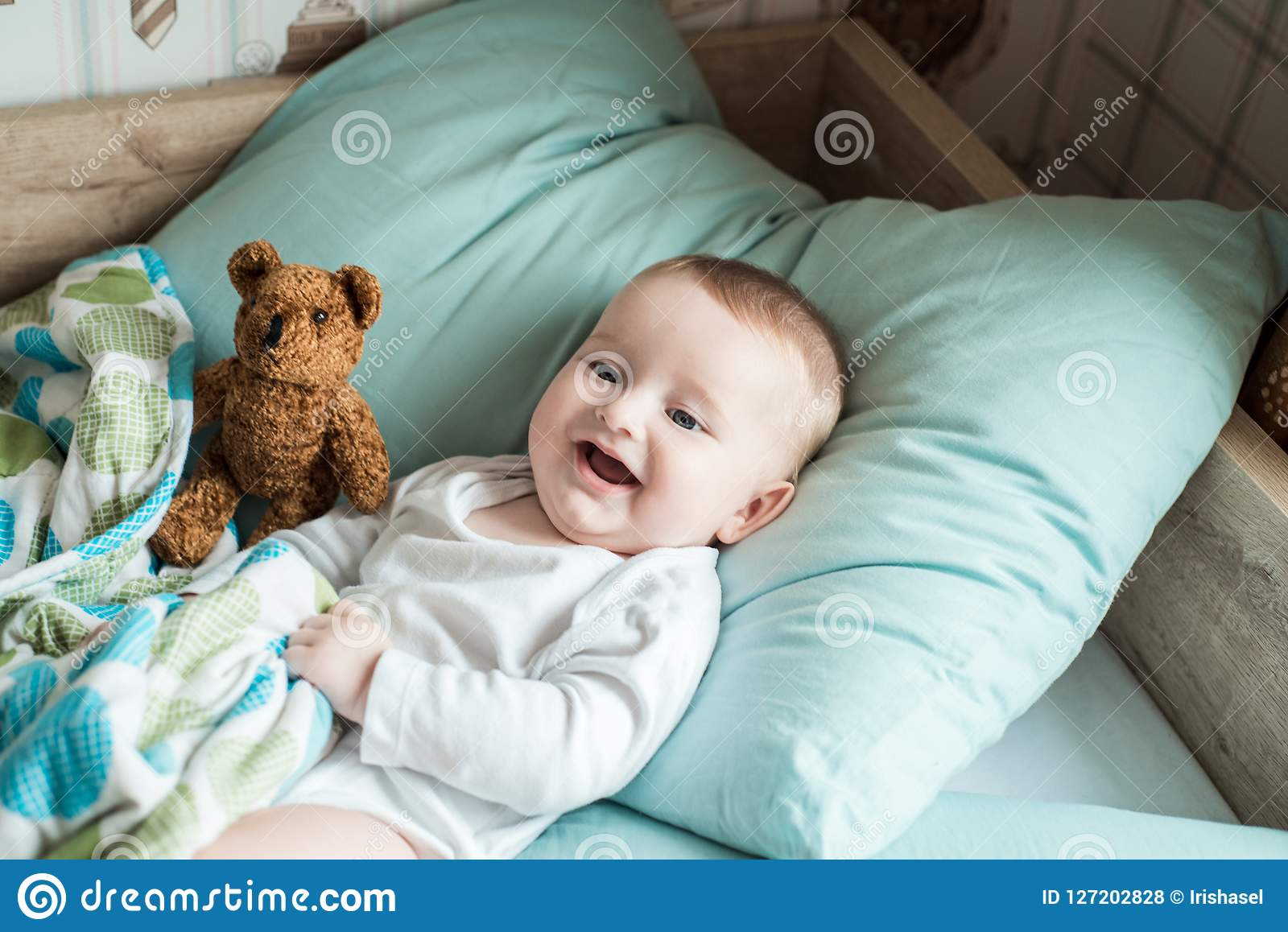 One Year Old Baby Lying In Bed With A Plush Teddy Bear Stock Photo