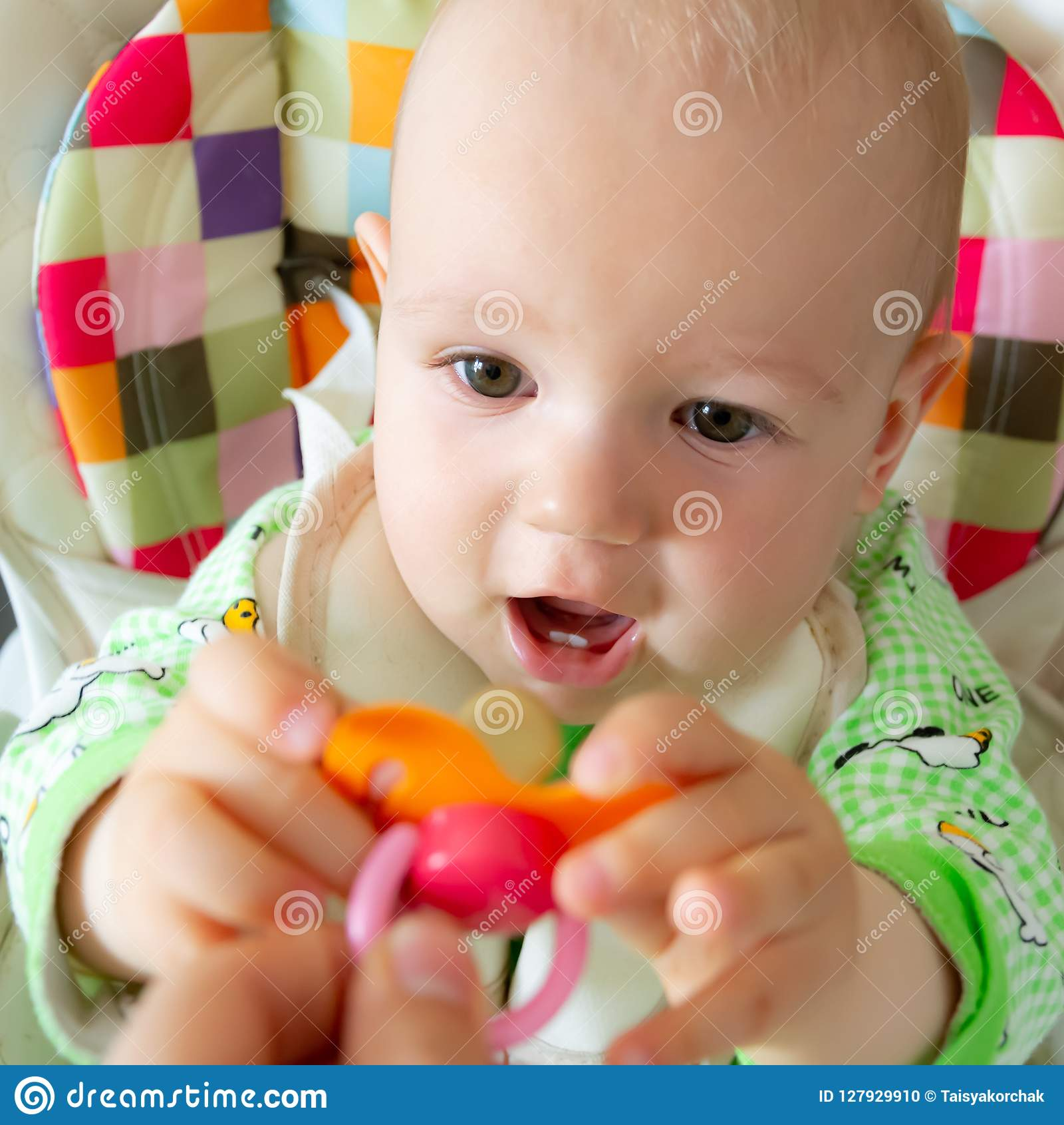 One year old baby nibbles / sucks on a rubber nipple because his teeth are being cut. Little cheerful boy in a light green suit wi