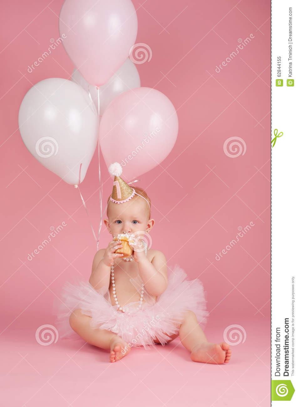 A Portrait Of One Year Old Baby Girl Wearing Pink Tutu String Pearls And Birthday Hat She Is Sitting Eating Cupcake On