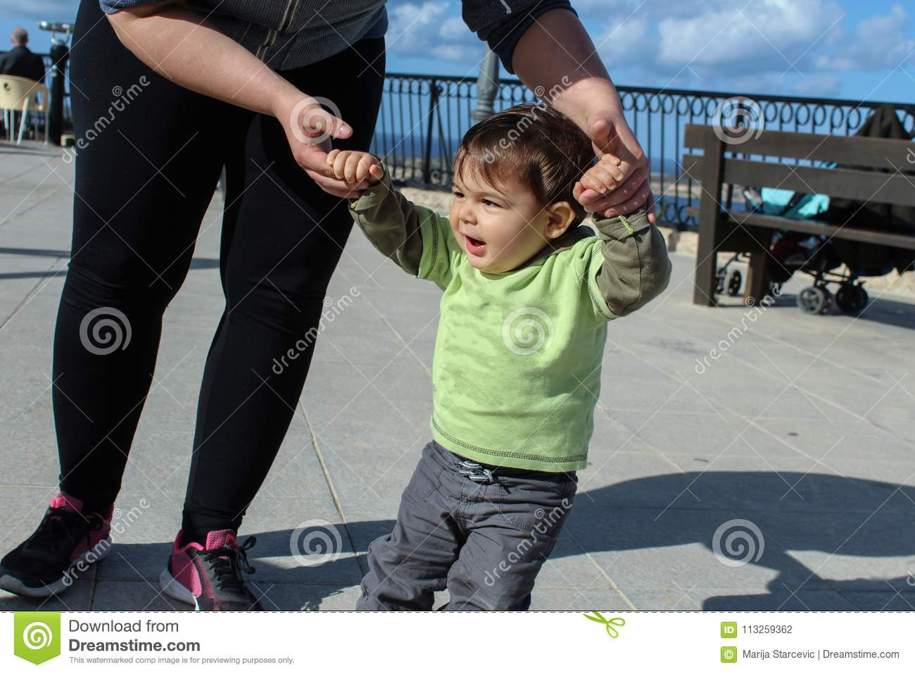 One year old todler learning how to walk with mother