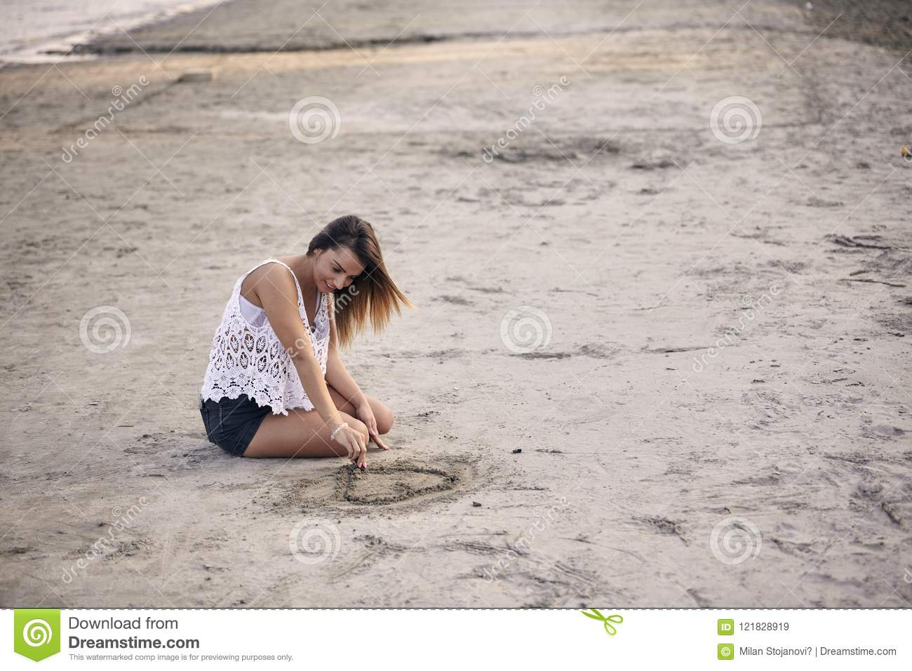 One young beautiful girl alone sitting in sand drawing with stick
