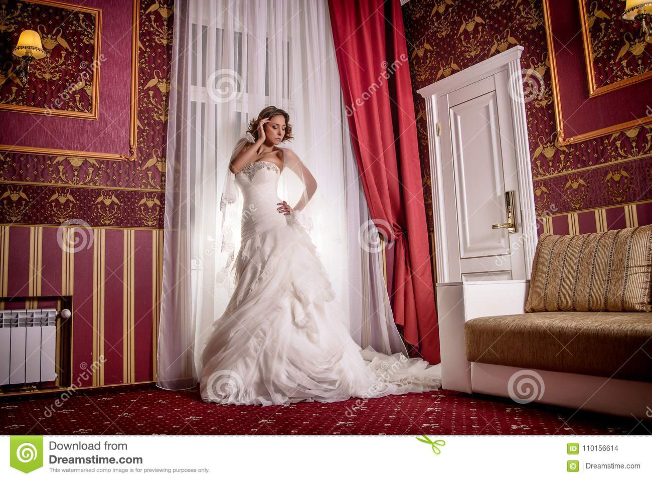 Beautiful model in wedding dress posing nicely in the motion in studio photo session.