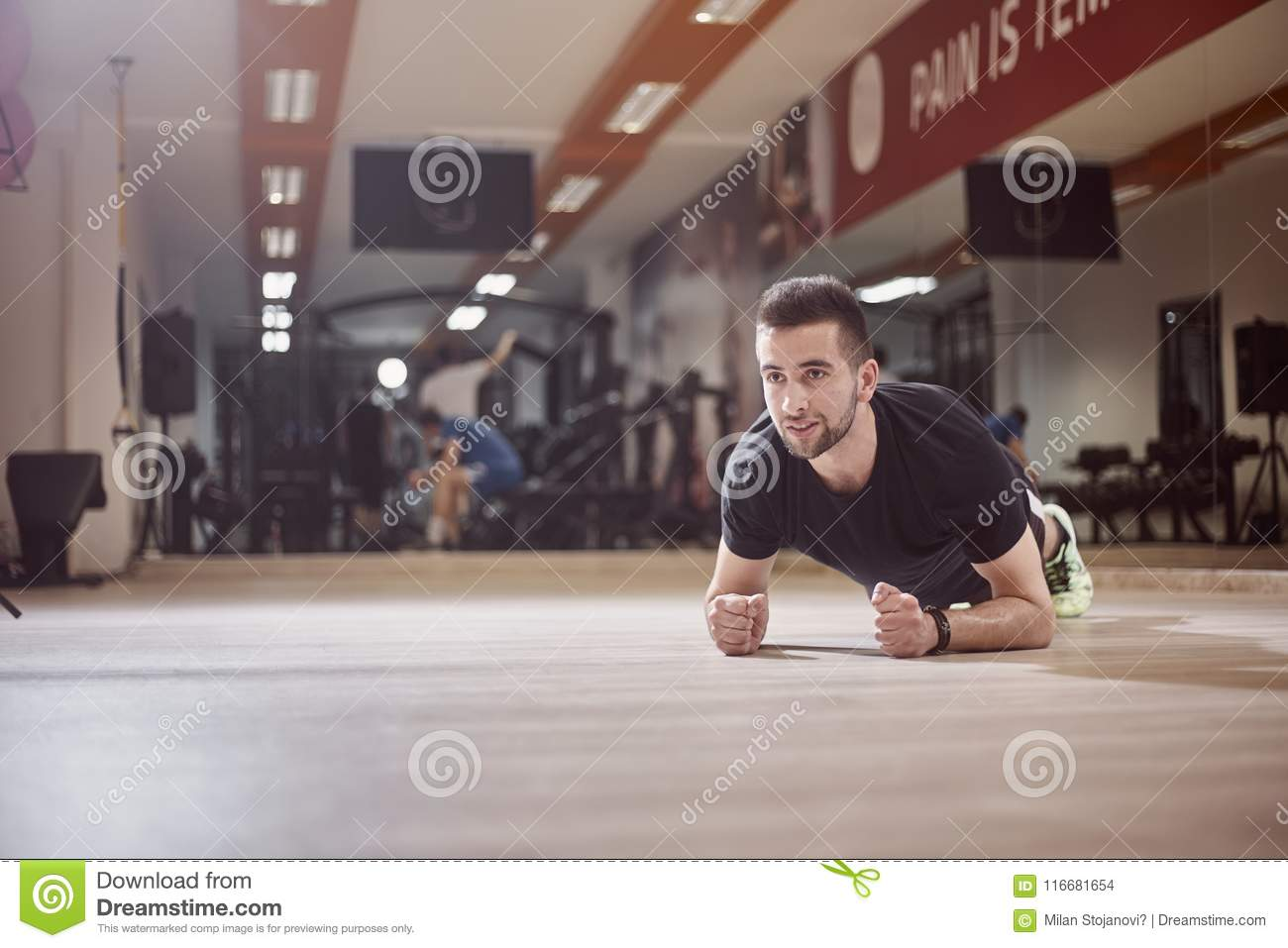 One young man, looking away, plank exercise, gym floor,