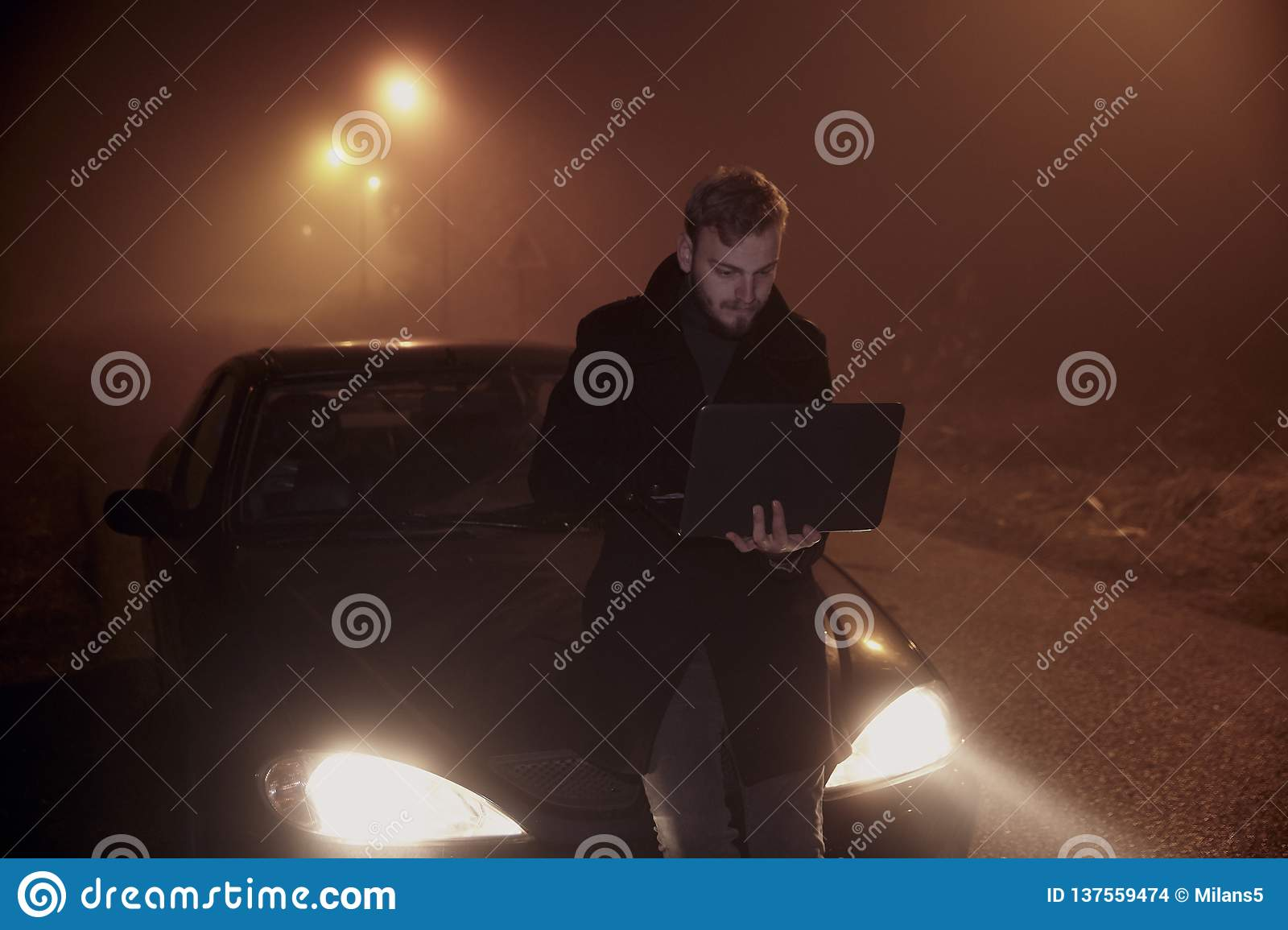 One young man using his laptop computer, on a car hood. It`s dark and night time, in rural area