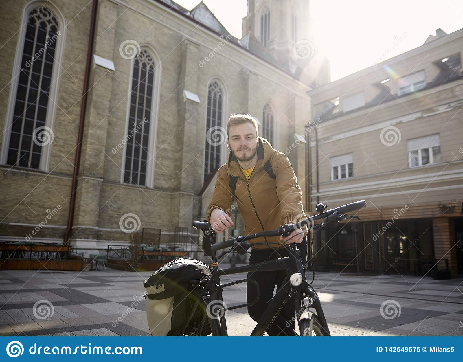 One young man, 20-29 years old, posing with his bicycle in a beautiful city square in Europe, Serbia, Novi Sad