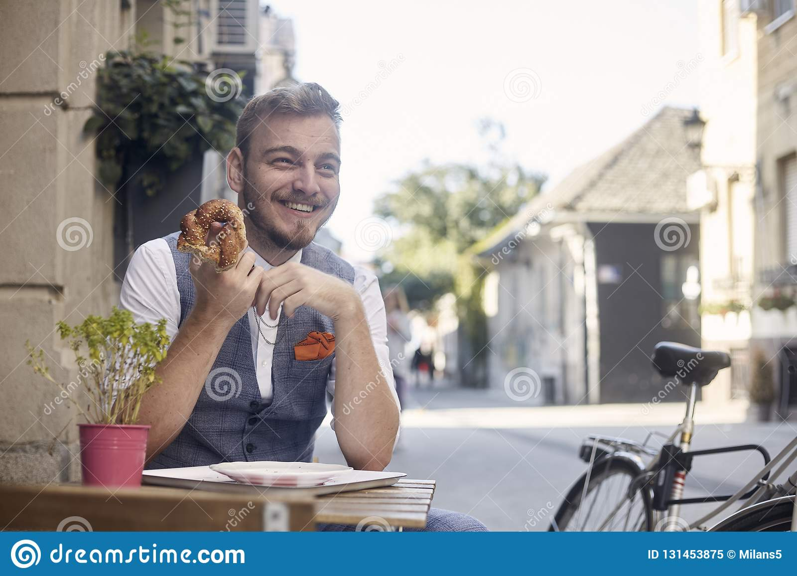 One young smiling man, 20-29 years old, wearing hipster suit, siting on street, eating pretzel in front of bakery outdoors. acting